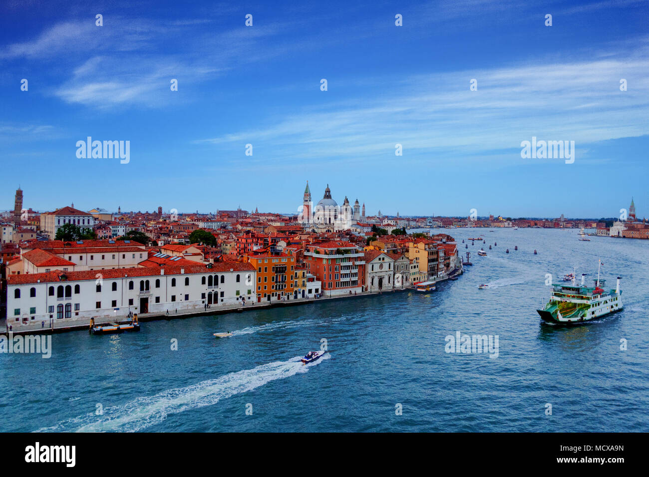 A Large Ferry and Many Small  Boats in the Canale Della Giudecca - Stock Image