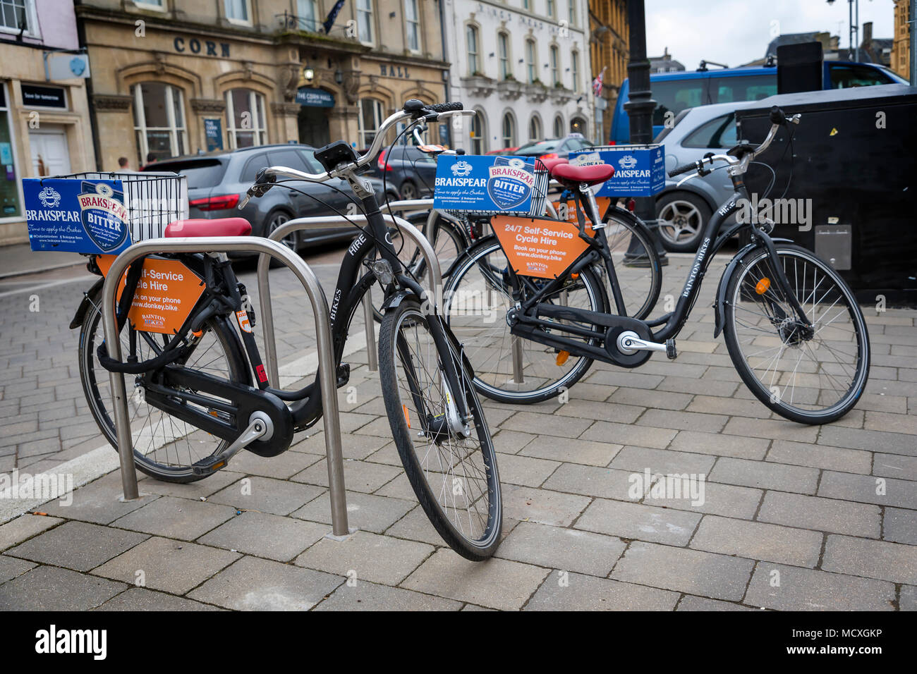 Donkey bikes chained to bike posts in Cirencester's town centre ready for hire on 07 April 2018 Stock Photo