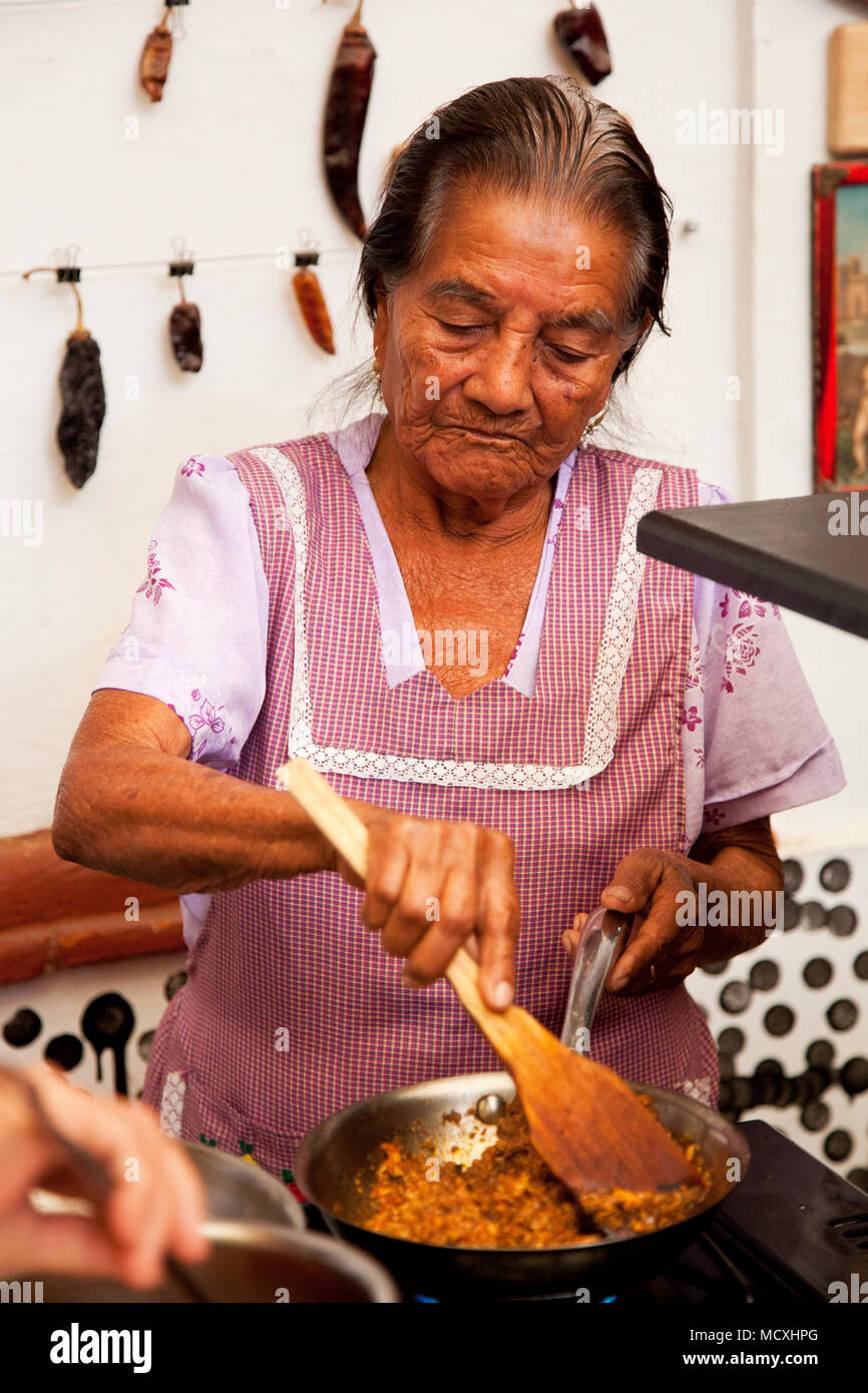 Grandmother of Chef José Luis Diaz cooking enchiladas de san pedro totolapam (meat -illed tortillas with chile sauce) Restaurante Chilhuacle Rojo,  Oa Stock Photo