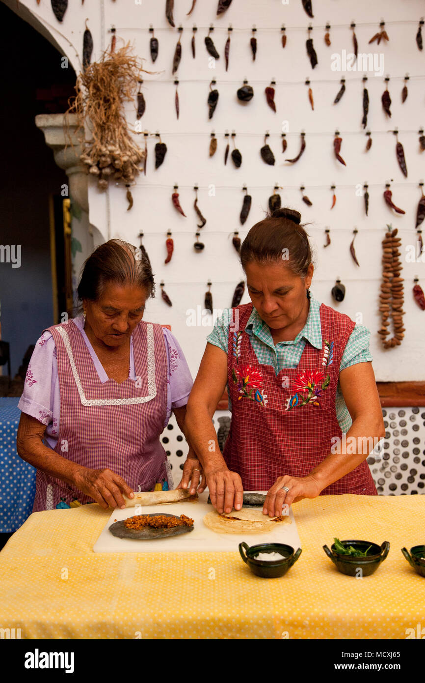 Grandmother, and mother of Chef José Luis Diaz cooking enchiladas de san pedro totolapam (meat-filled tortillas with chile sauce)  Restaurante Chilhua Stock Photo