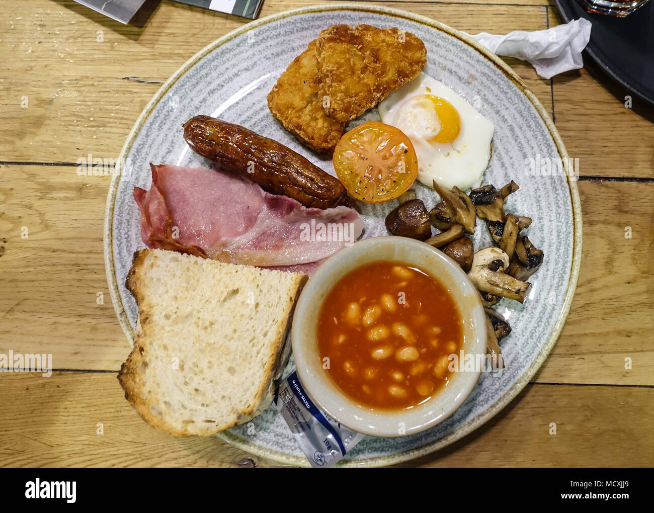 A view of a full English breakfast at a cafe with fried egg, sausage, bacon, fried mushrooms, hasb browns and baked beans. - Stock Image