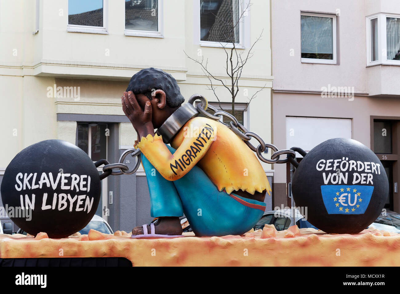 Migrant from Africa, double chained, slavery sponsored by the EU, political caricature, motto caravan during Carnival Monday - Stock Image