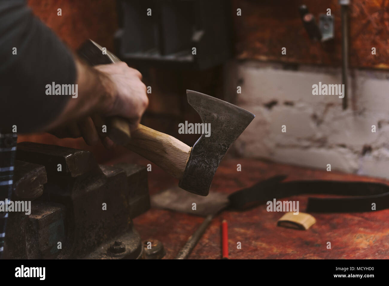 Man works in carpentry workshop. He straightens ax blade on wooden handle with hammer. Men at work. Hand work. - Stock Image