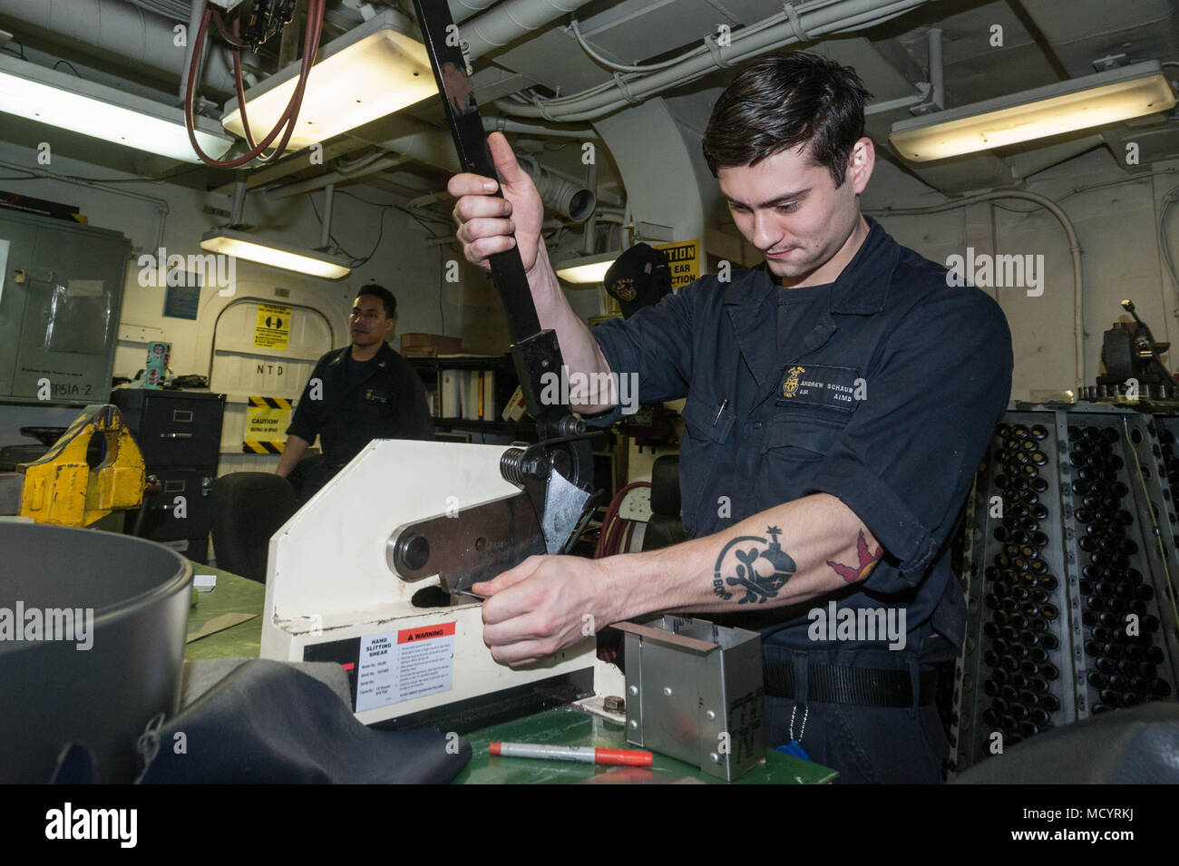 Aviation Structural Mechanic Airman Andrew Shaub, from Massillon, Ohio, uses a hand slitting shear to cut aluminum aboard the amphibious assault ship USS Wasp (LHD 1). The Wasp Expeditionary Strike Group is conducting a regional patrol meant to strengthen regional alliances, provide rapid-response capability, and advance the Up-Gunned ESG concept. (U.S. Navy photo by Mass Communication Specialist 2nd Class Desmond Parks/released). - Stock Image
