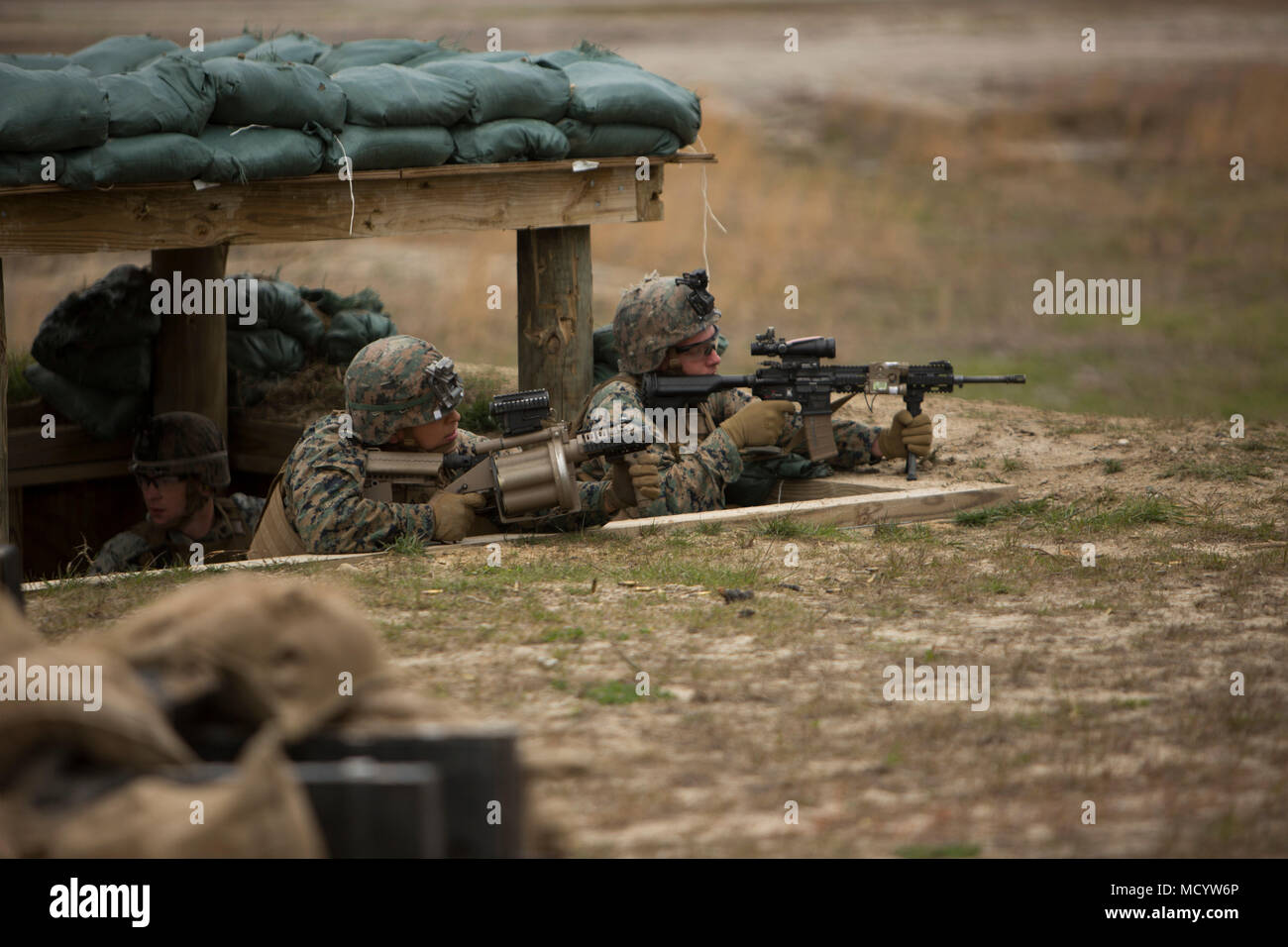 U.S. Marines Corps with India Company, 3rd Battalion, 2nd Marine Regiment, 2nd Marine Division, provide suppressive during a live-fire platoon attack at Range G-29  on Camp Lejeune, N.C., March 7, 2018. 2nd Marine Division provided funding and material for the creation of Range G-29 and tasked Marines with 2nd Combat Engineer Battalion to finalize the production of the range. (U.S. Marine Corps photo by Cpl. Justin X. Toledo). - Stock Image