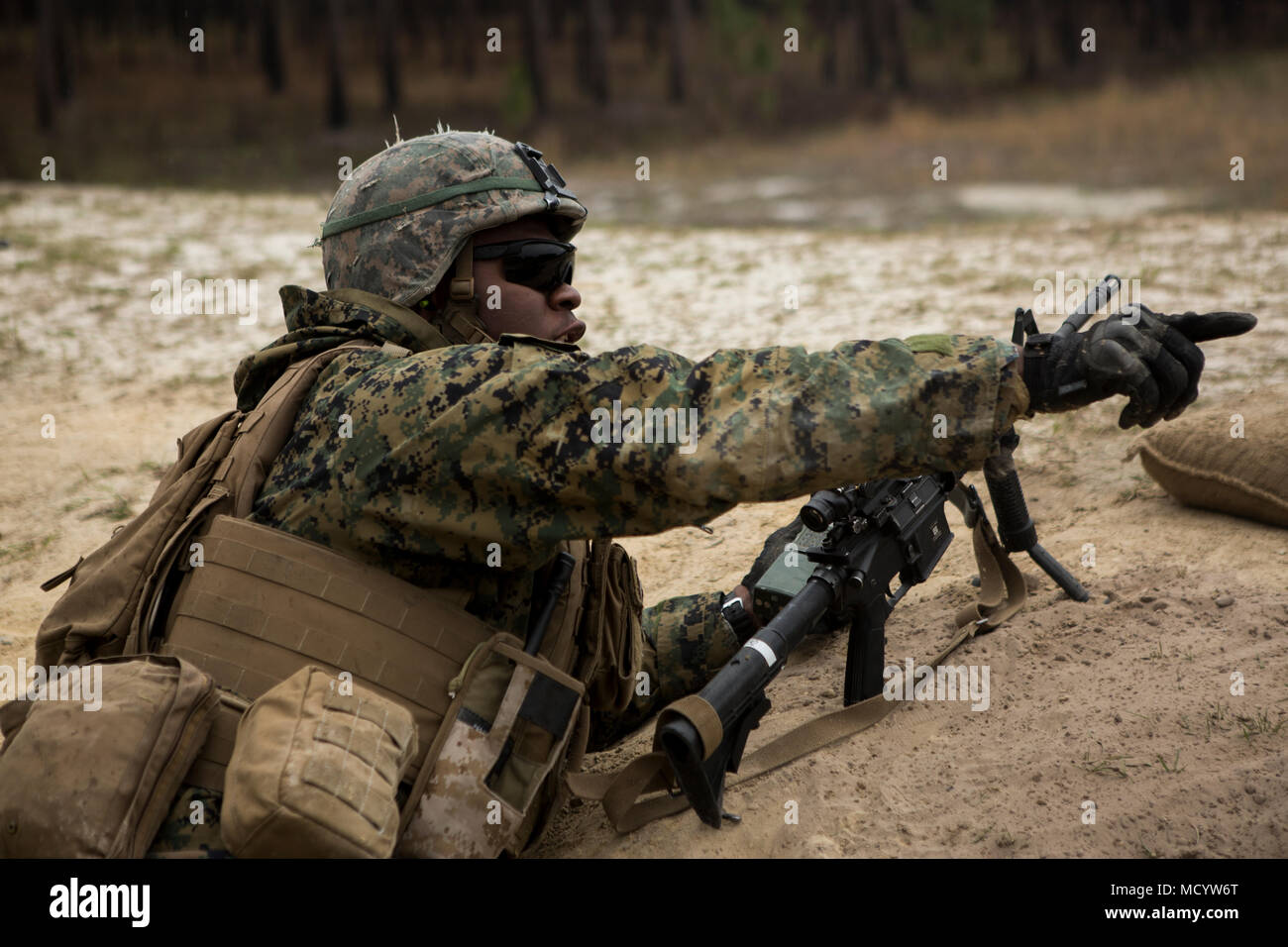 A U.S. Marine with Company L, 3rd Battalion, 2nd Marine Regiment, 2nd Marine Division, shouts out commands during a live fire platoon attack on the new G29 on Camp Lejeune, N.C., March 6, 2018. 2nd Marine Division provided funding and material for the creation of G-29, then used 2nd Combat Engineer Battalion equipment and operators to finalize the production of the range. (U.S. Marine Corps photo by Pfc. Nathaniel Hamilton) - Stock Image