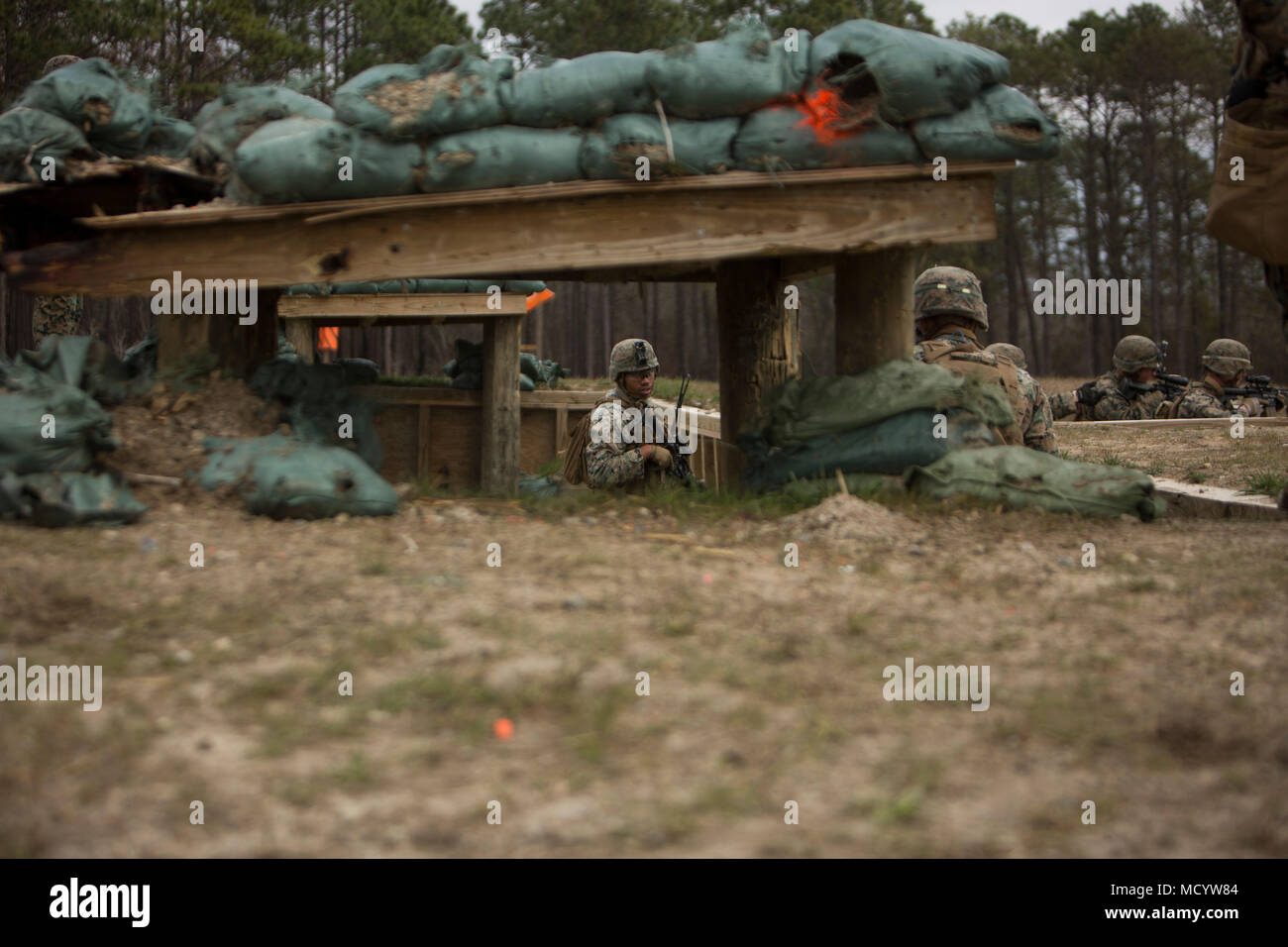 U.S. Marines with India Company, 3rd Battalion, 2nd Marine Regiment, 2nd Marine Division, secure trenches during a live-fire platoon attack at Range G-29 on Camp Lejeune, N.C., March 7, 2018. 2nd Marine Division provided funding and material for the creation of Range G-29 and tasked Marines with 2nd Combat Engineer Battalion to finalize the production of the range. (U.S. Marine Corps photo by Cpl. Justin X. Toledo). - Stock Image