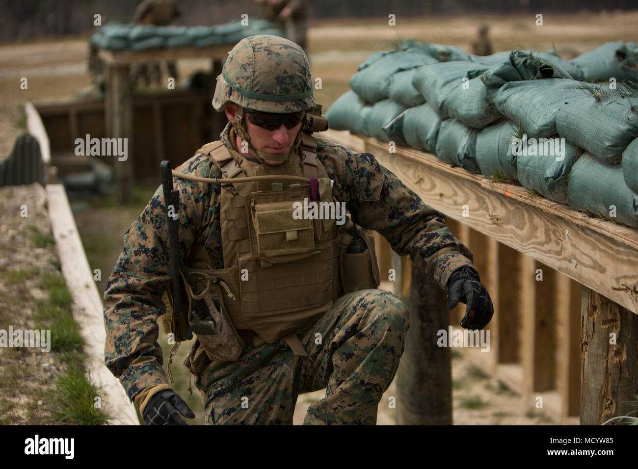 A U.S. Marine with India Company, 3rd Battalion, 2nd Marine Regiment, 2nd Marine Division, exits a trench during a live-fire platoon attack at Range G-29,  on Camp Lejeune, N.C., March 7, 2018. 2nd Marine Division provided funding and material for the creation of Range G-29 and tasked Marines with 2nd Combat Engineer Battalion to finalize the production of the range. (U.S. Marine Corps photo by Cpl. Justin X. Toledo). - Stock Image