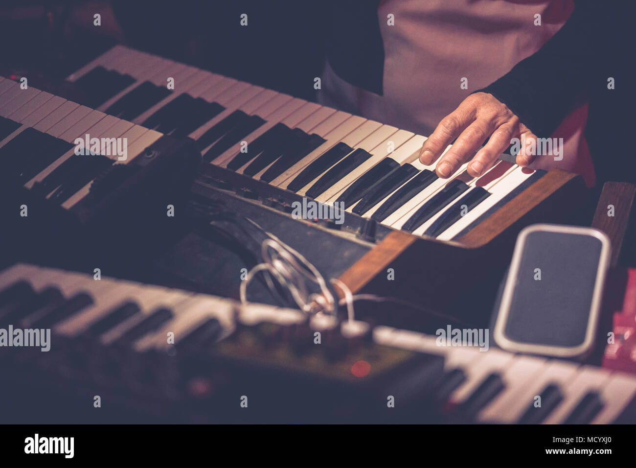 Hands of a musician while playing a keyboard of vintage synth - Stock Image