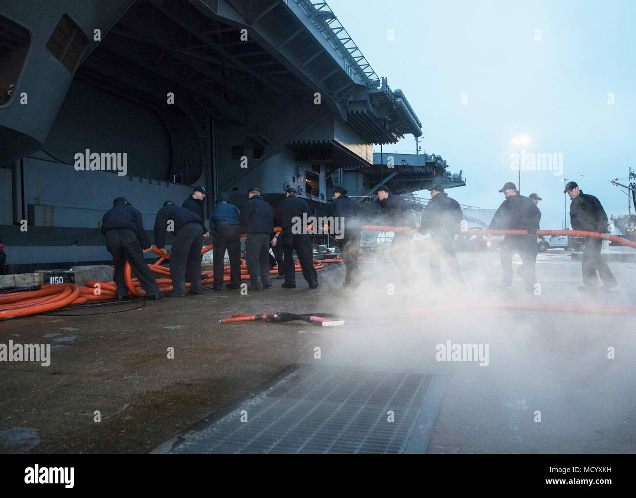 180307-N-YP246-0051 NORFOLK (March 7, 2018) Sailors disconnect shore power cables from the Nimitz-class aircraft carrier USS Abraham Lincoln (CVN 72) in preparation for getting underway.  (Mass Communication Specialist Seaman Darcy McAtee/Released) - Stock Image