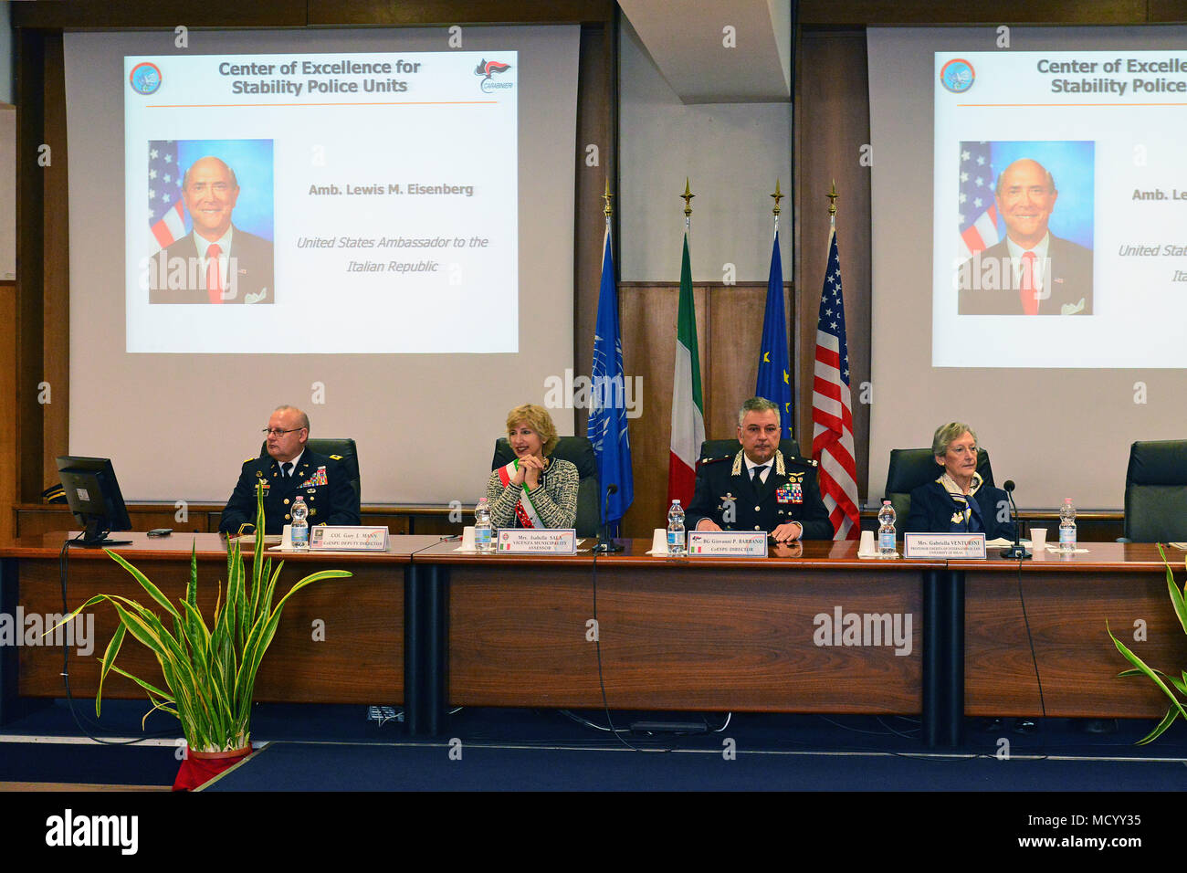 A video statement by Ambassador Lewis M. Eisenberg, United States Ambassador to the Italian Republic, plays on a projector screen for attendees during the opening ceremony of the 8th Gender Protection in Peace Operations Course at the Center of Excellence for Stability Police Units (CoESPU) in Vicenza, Italy, Mar. 8, 2018. The event brought together military and civic leaders from the local community to celebrate International Women's Day. (U.S. Army Photo by Paolo Bovo) Stock Photo