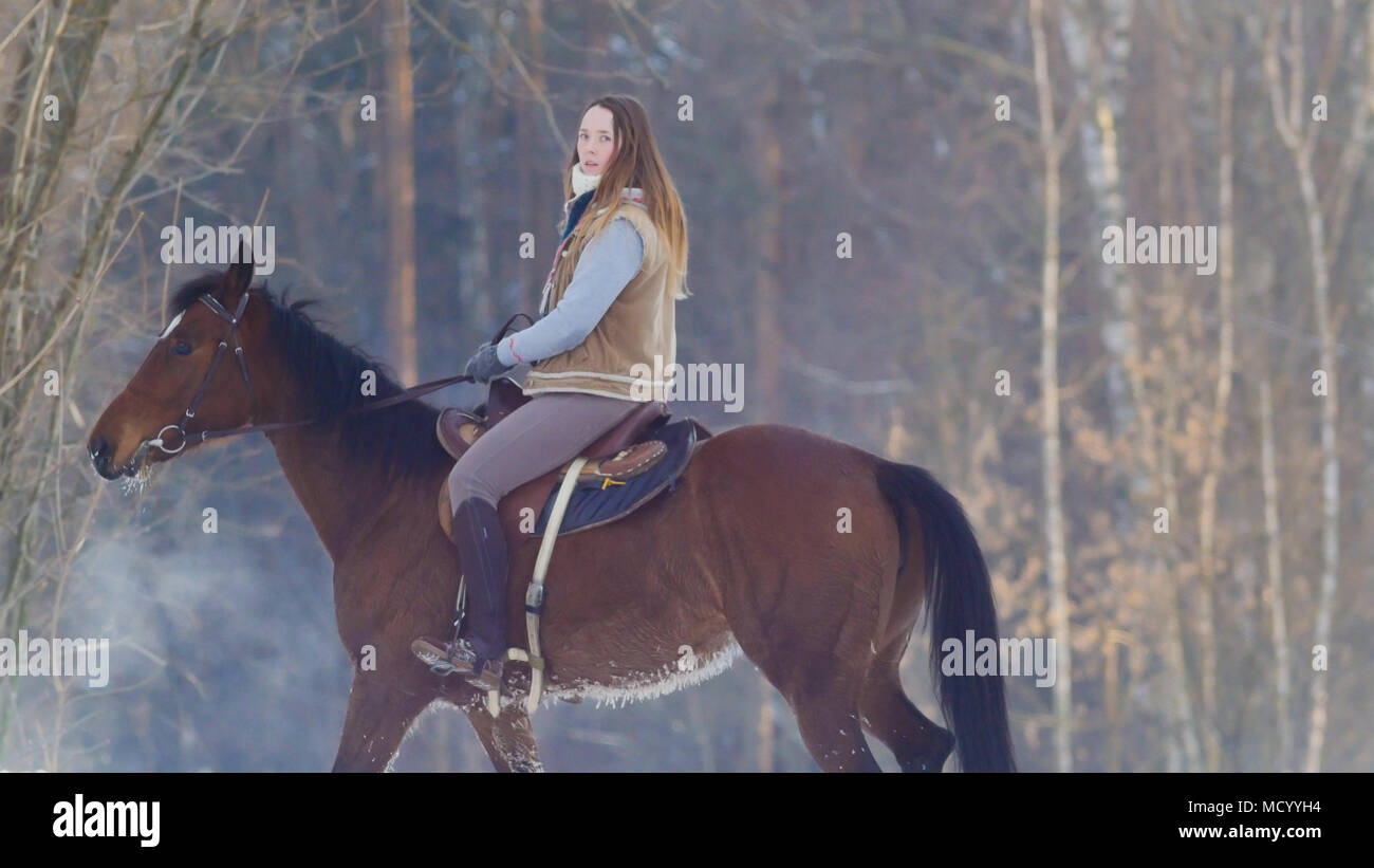 Longhaired Female Rider Wild And Fast Riding Black Horse Through The Snow Stock Photo Alamy