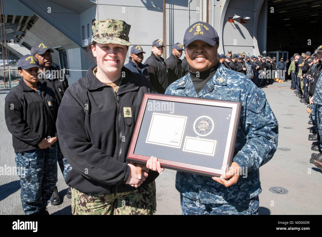 NORFOLK, Va. (Mar. 9, 2018) -- Chief Electrician's Mate (Nuclear) Sarah Gideon receives a plaque from USS Gerald R. Ford's (CVN 78) Chiefs Mess as she departs the command. (U.S. Navy photo by Mass Communication Specialist 3rd Class Joshua Murray) - Stock Image