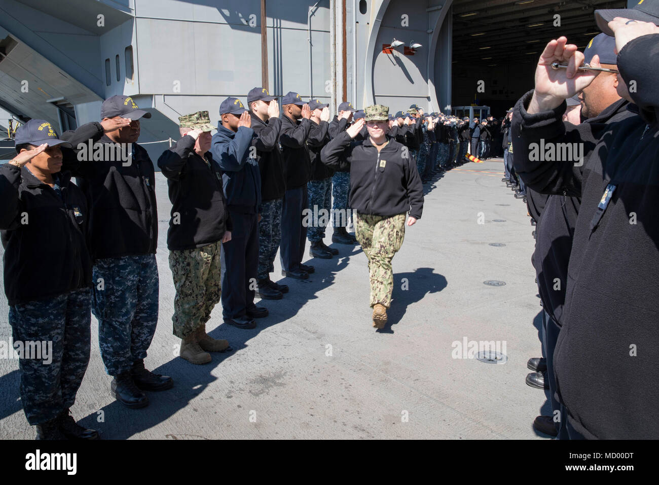NORFOLK, Va. (Mar. 9, 2018) -- Chief Electrician's Mate (Nuclear) Sarah Gideon returns the salute of USS Gerald R. Ford (CVN 78) Sailors as she departs the command. (U.S. Navy photo by Mass Communication Specialist 3rd Class Joshua Murray) - Stock Image