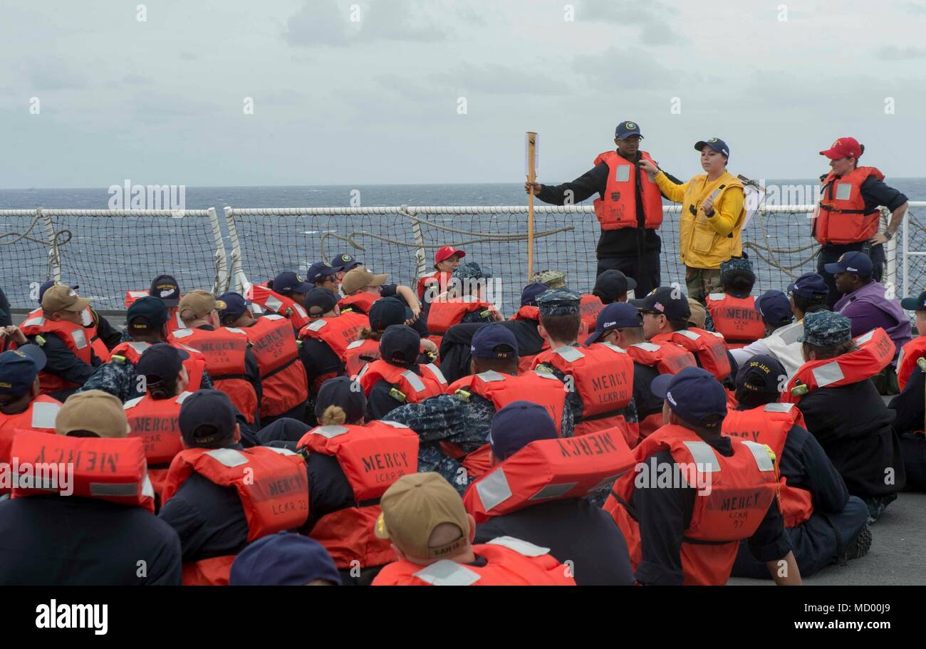 180308-N-NH199-0082  PACIFIC OCEAN (March 8, 2018) Sailors learn how to don a life jacket during an abandon ship drill aboard Military Sealift Command hospital ship USNS Mercy (T-AH 19). Mercy is deployed in support of Pacific Partnership 2018 (PP18). PP18's mission is to work collectively with host and partner nations to enhance regional interoperability and disaster response capabilities, increase stability and security in the region, and foster new and enduring friendships across the Indo-Pacific Region. Pacific Partnership, now in its 13th iteration, is the largest annual multinational hum - Stock Image