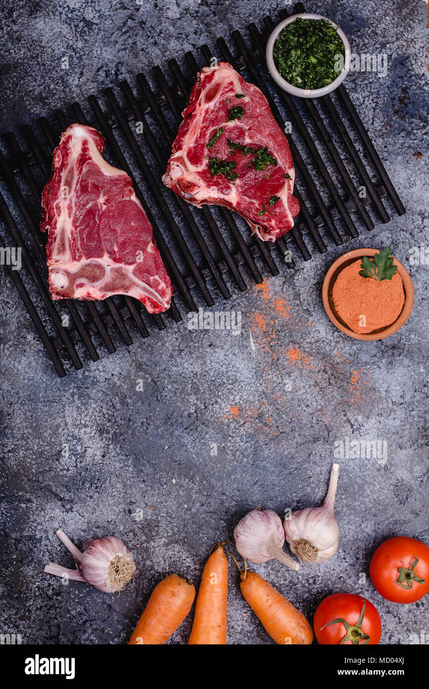 top view of raw meat with spices and vegetables on concrete table - Stock Image
