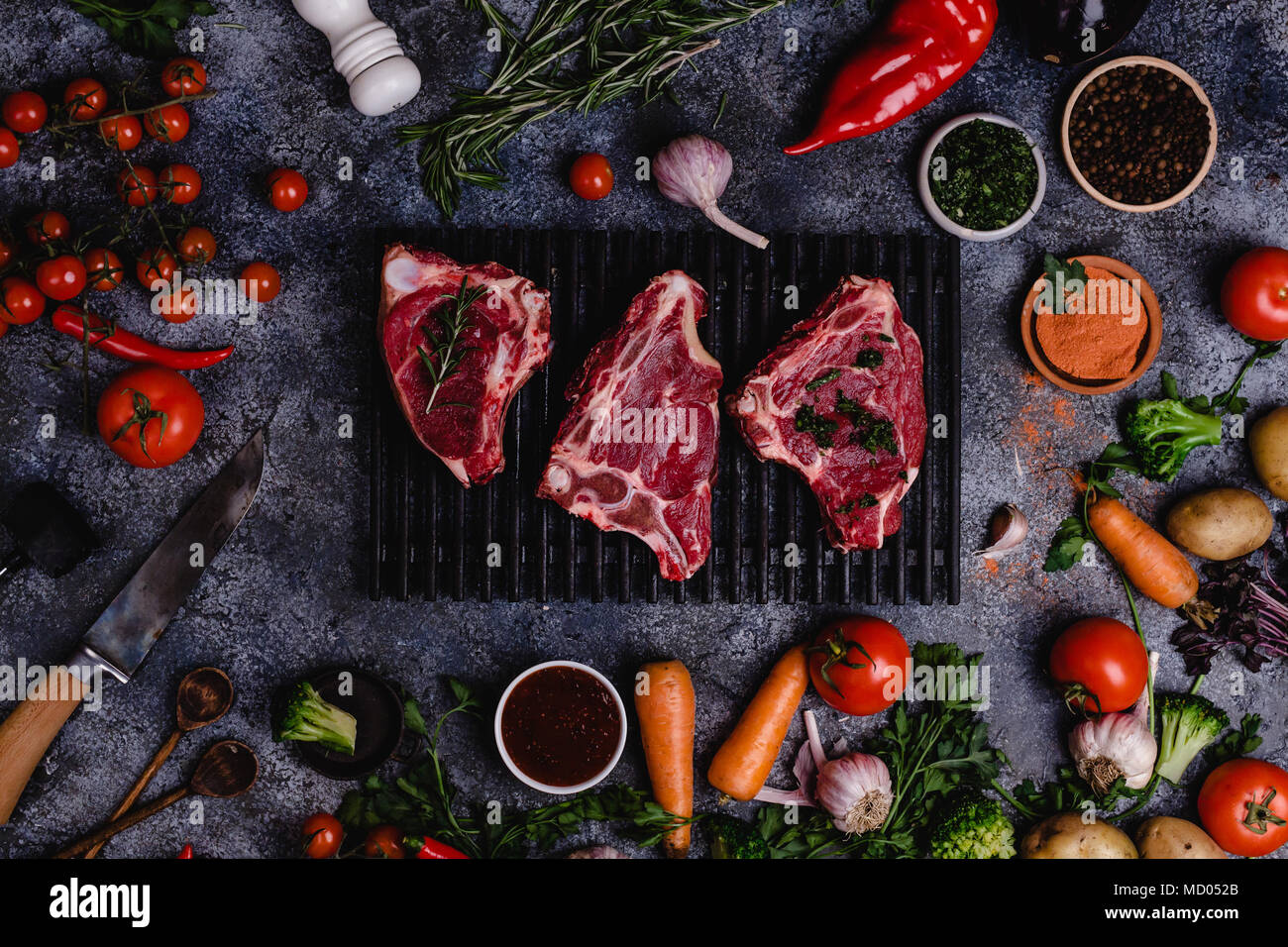 top view of raw meat slices and vegetables on black concrete surface - Stock Image