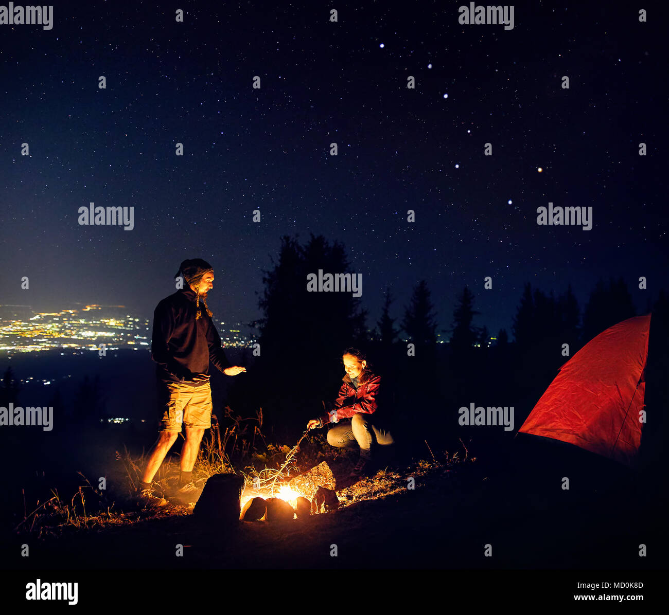 Happy couple hikers warm they hands near campfire under night sky with stars and city lights at background. - Stock Image