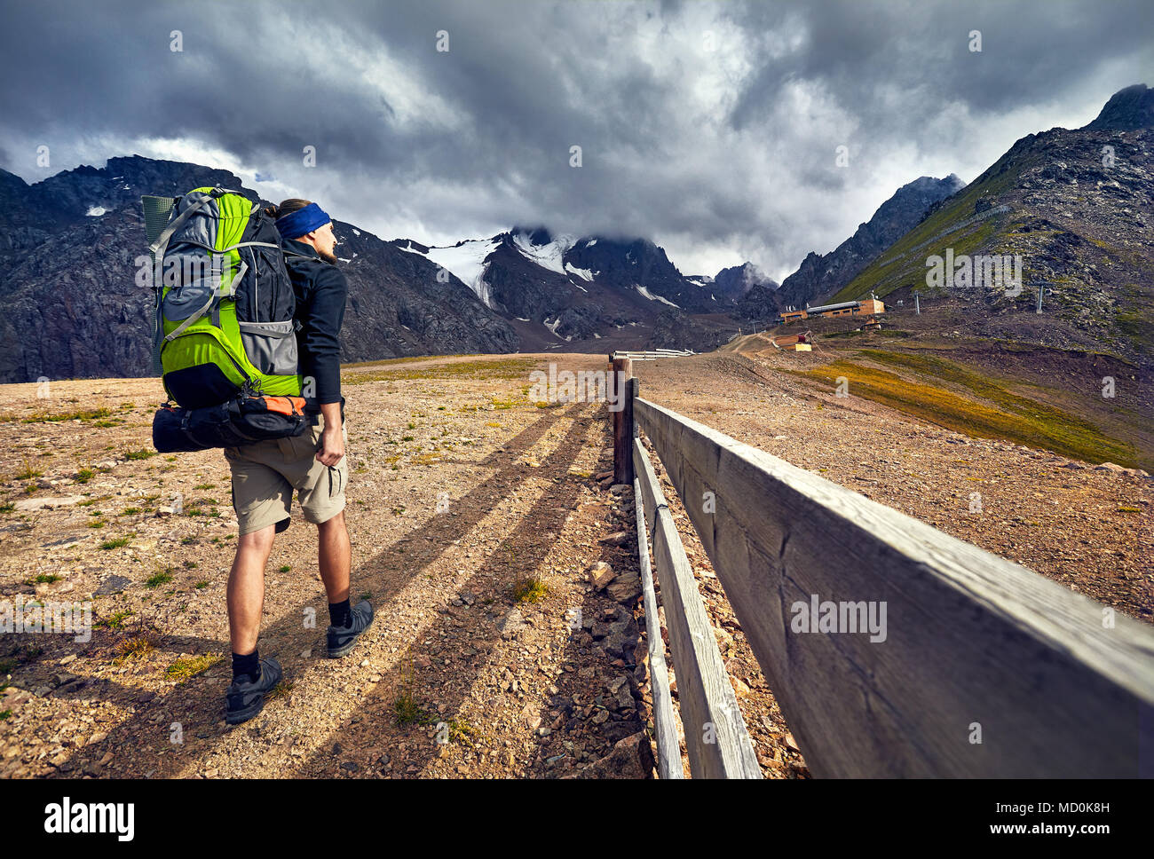 Hiker in with big green backpack walking to the snowy mountains at overcast dark sky background in Shymbulak Ski Resort in Kazakhstan - Stock Image