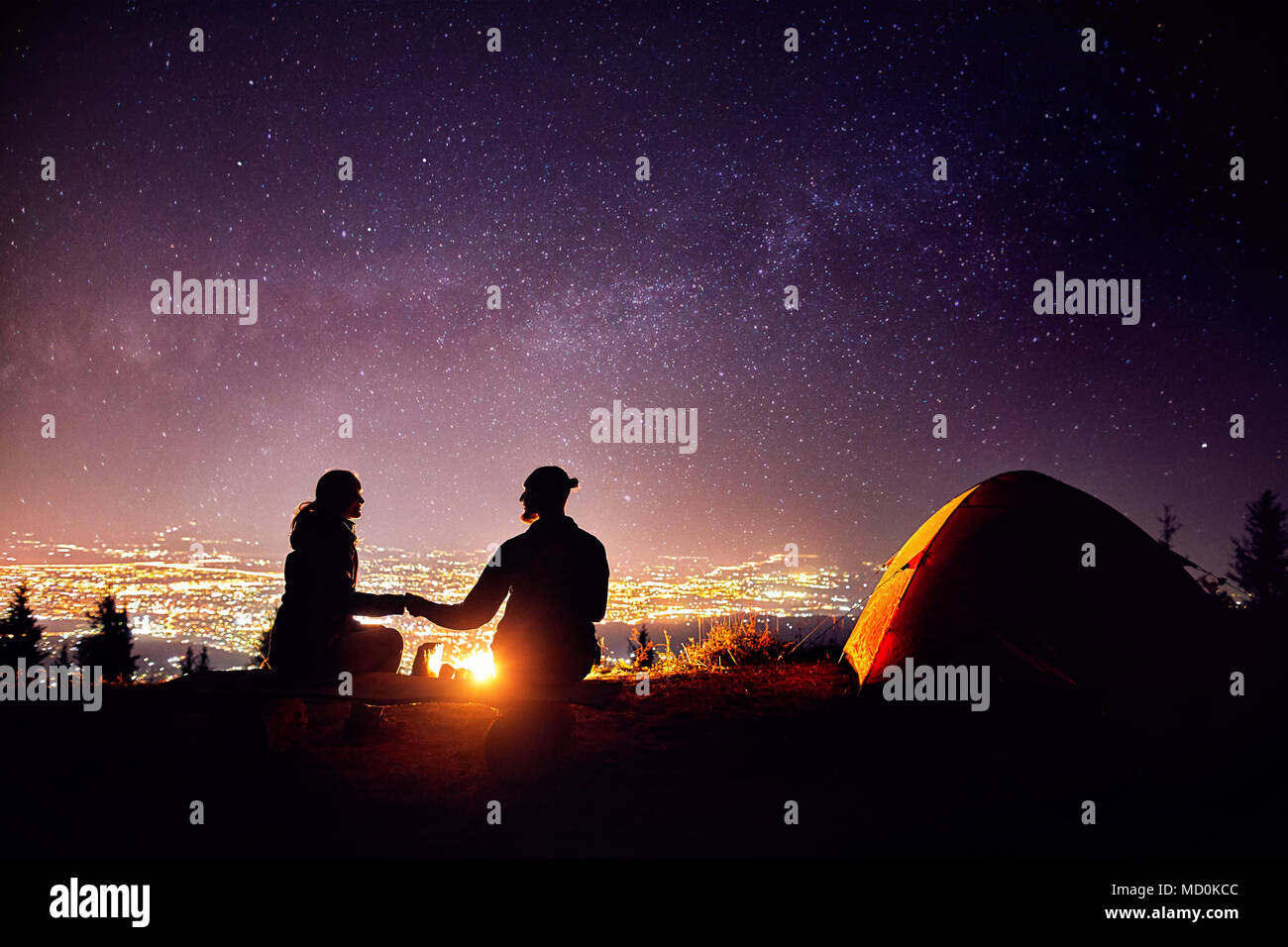 Happy couple in silhouette sitting near campfire and orange tent. Night sky with milky way stars and city lights at background. - Stock Image