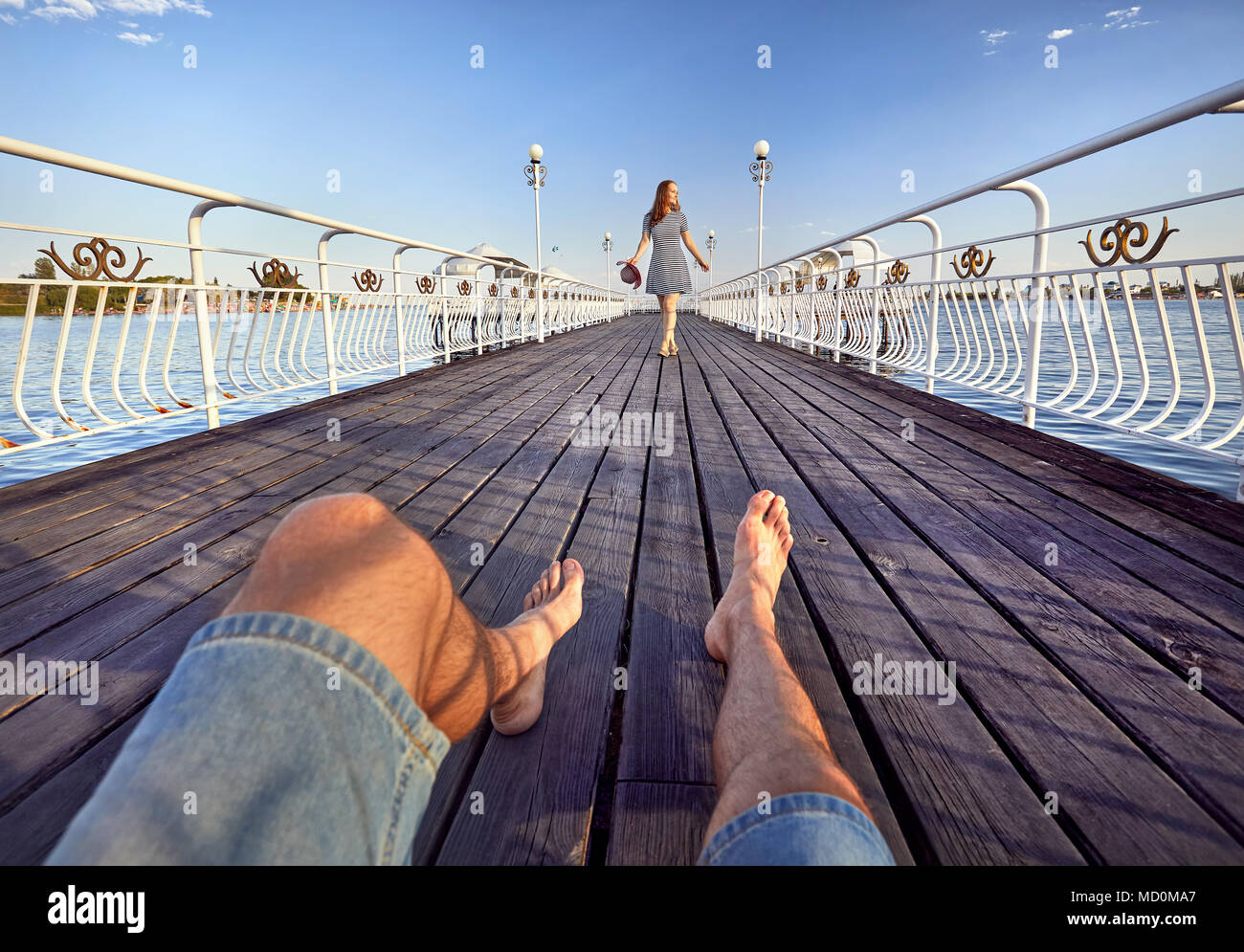 Woman in striped dress with red hat going to his boyfriend by on the pier in the beach - Stock Image