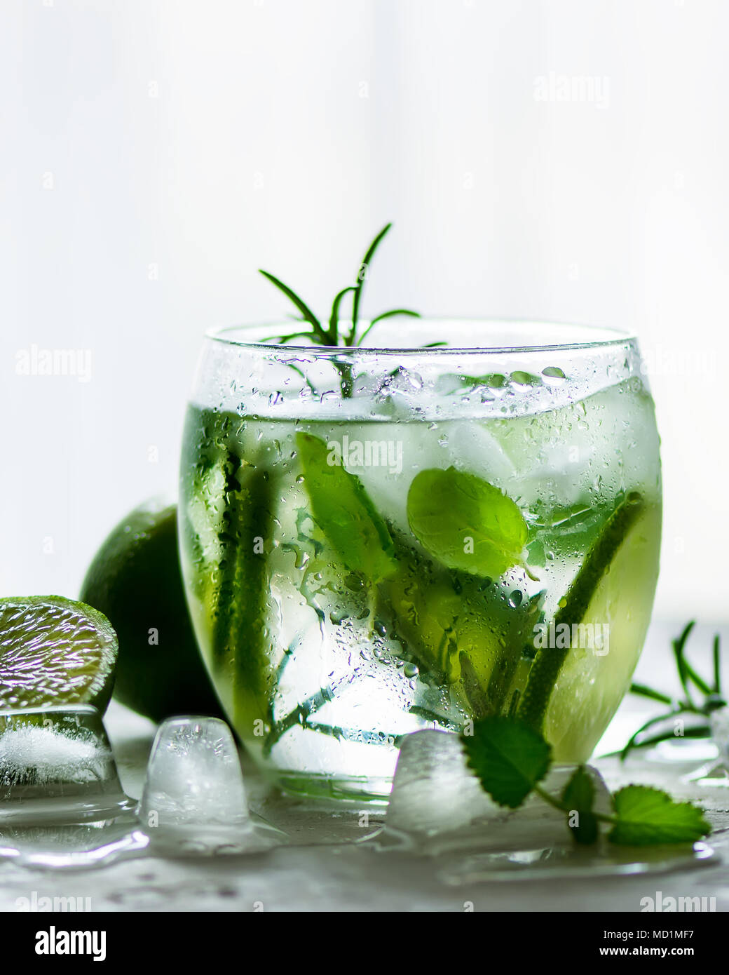 Homemade lime lemonade with cucumber, rosemary and ice, white background. Cold beverage for hot summer day. Copyspace. Banner. - Stock Image