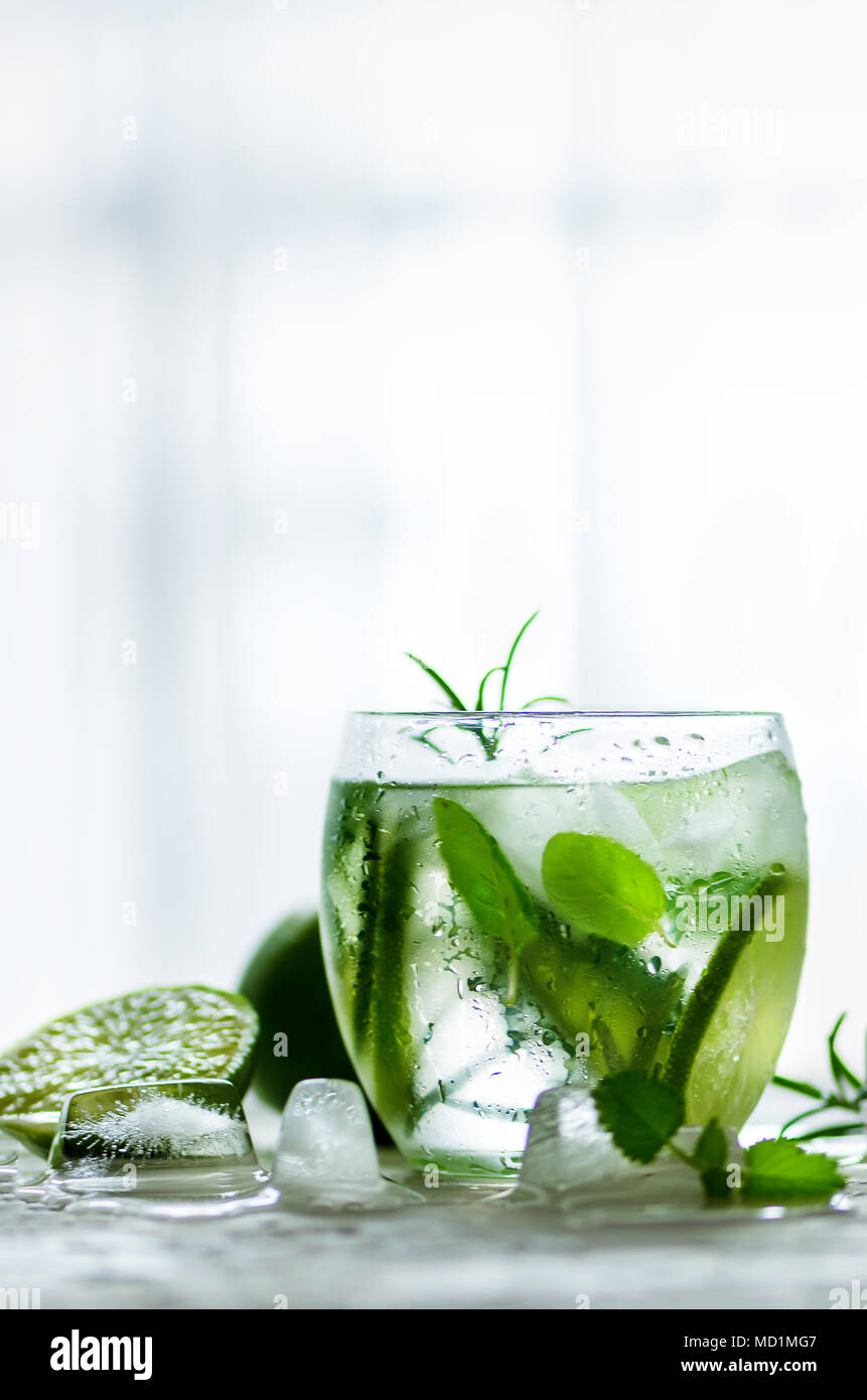 Homemade lime lemonade with cucumber, rosemary and ice, white background. Cold beverage for hot summer day. Copyspace. - Stock Image