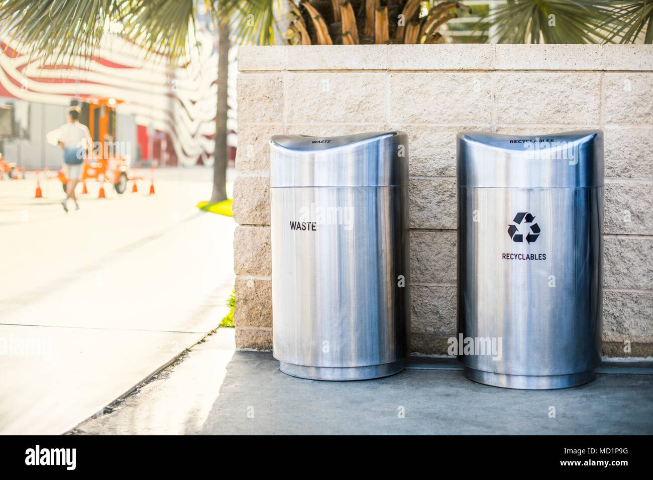 Separate garbage bins for recycled trash and waste installed on a sidewalk on the city street - Stock Image