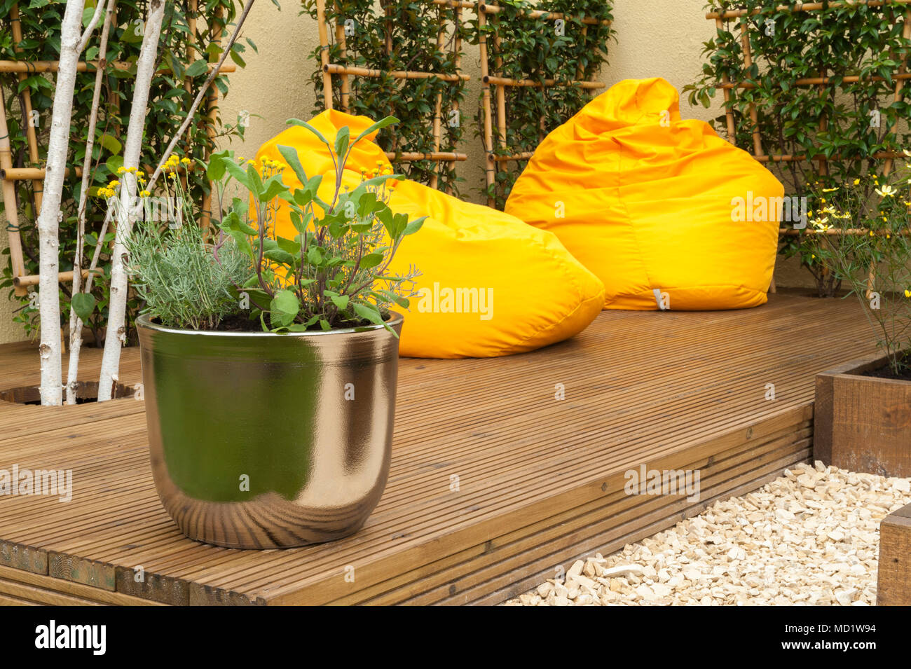 Close-up of pot plants & bright colourful, yellow beanbag chairs on timber decking - 'The Journey Garden' - RHS Flower Show, Tatton Park, England, UK - Stock Image