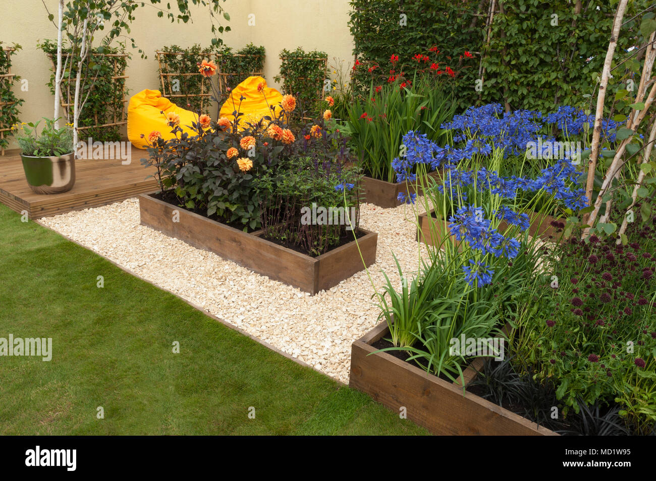 Bright colourful flowering plants in timber beds & yellow beanbag chairs on decking - 'The Journey Garden' - RHS Flower Show, Tatton Park, England, UK - Stock Image