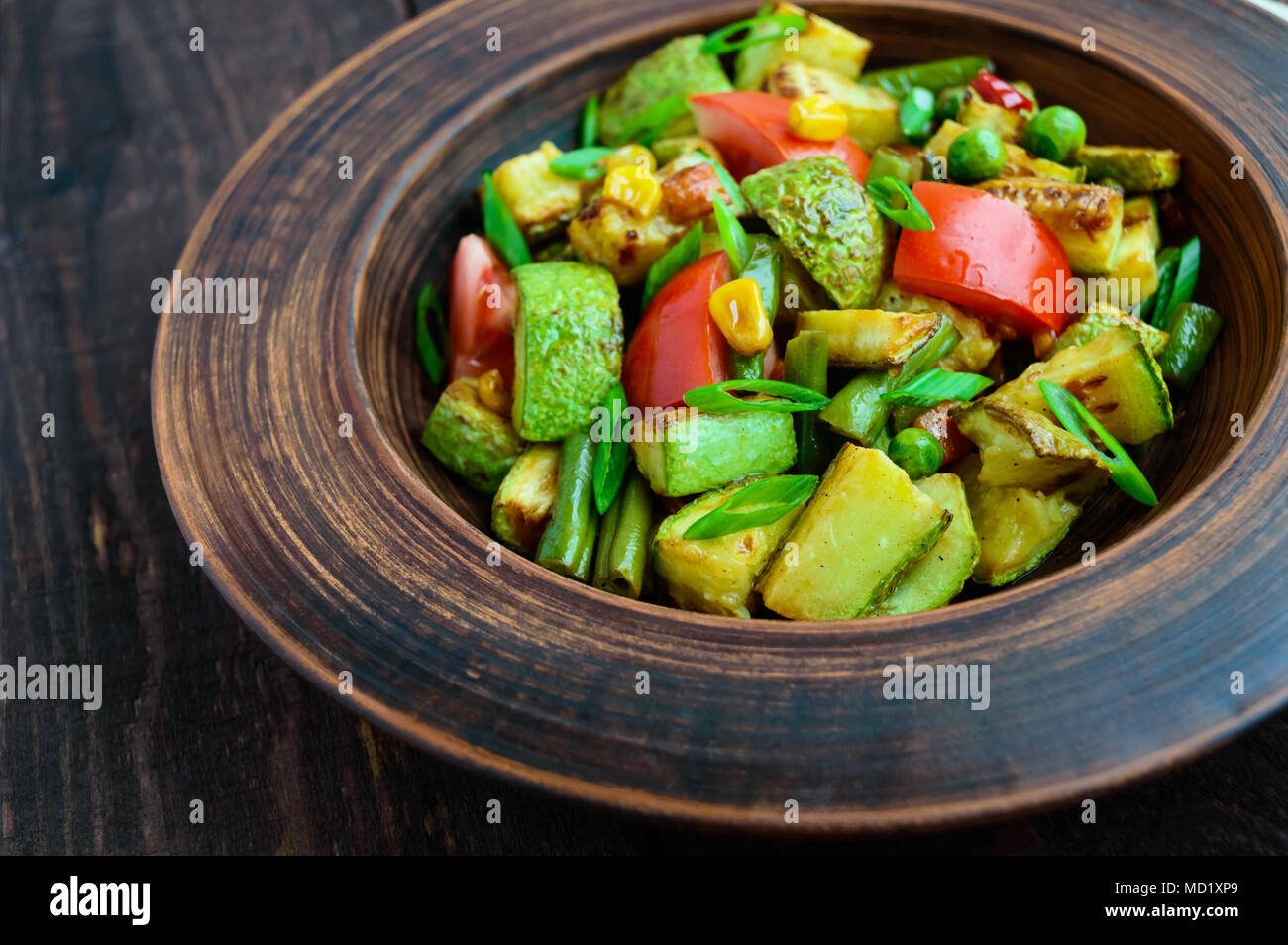 Dietary vegetarian salad with grilled zucchini, fresh tomatoes, sweet corn and herbs in a clay bowl on dark wooden background. - Stock Image