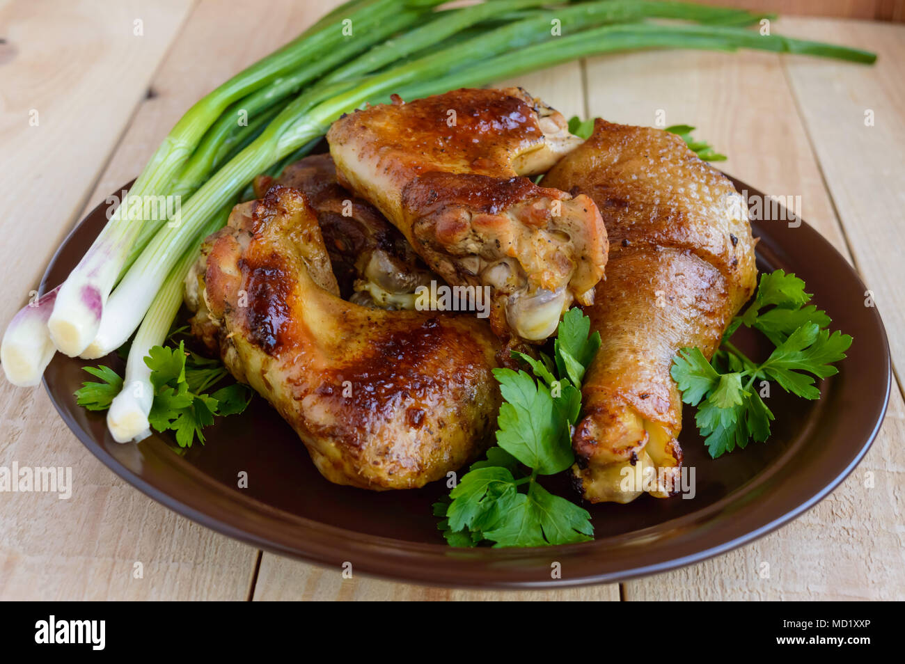 Roasted juicy chicken (legs, winglets) on a clay plate on a light wooden background - Stock Image