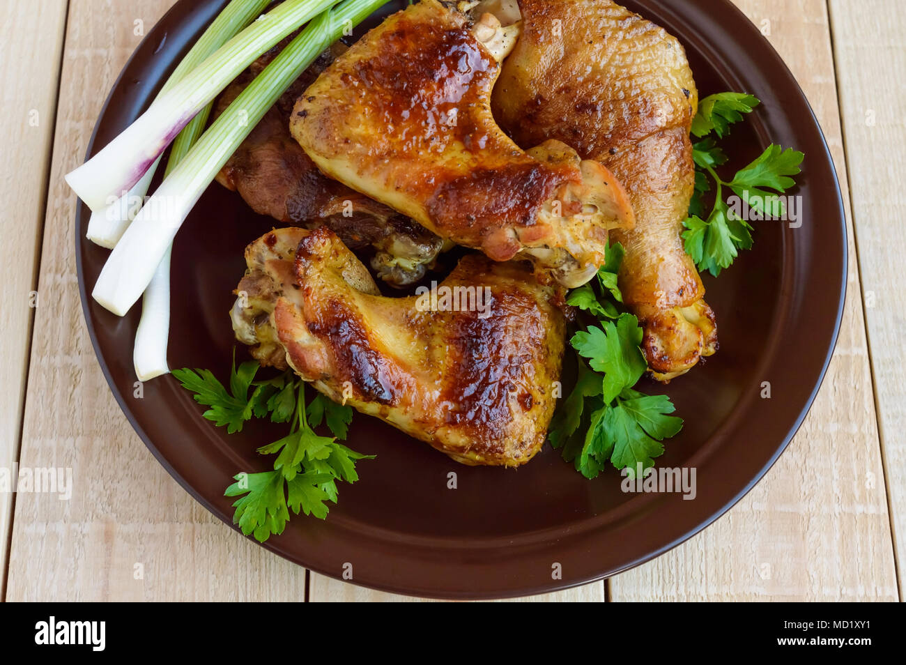 Roasted juicy chicken (legs, winglets) on a clay plate on a light wooden background. The top view - Stock Image