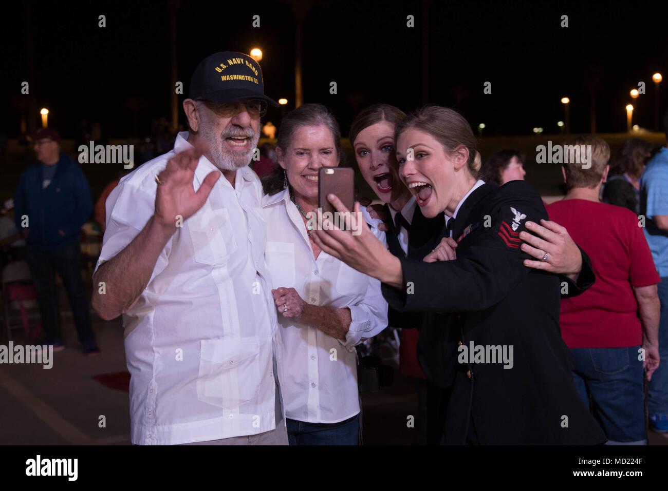 180312-N-NW255-1115 SUN CITY, Ariz. (March 12, 2018) Chief Musician Jennifer Stothoff, center, and Musician 1st Class Chelsi Ervien meet the parents of Chief Musician Amanda Cline, the Navy Band's head of productions. The four video conferenced with Cline, who is back home in Washington, D.C., after a performance by the U.S. Navy Band Sea Chanters at the Sun Bowl Amphitheatre in Sun City, Arizona. The Navy's official chorus is on an 18-day tour through California, Arizona and Nevada, connecting Americans to their Navy. (U.S. Navy photo by Senior Chief Musician Melissa Bishop/Released) Stock Photo