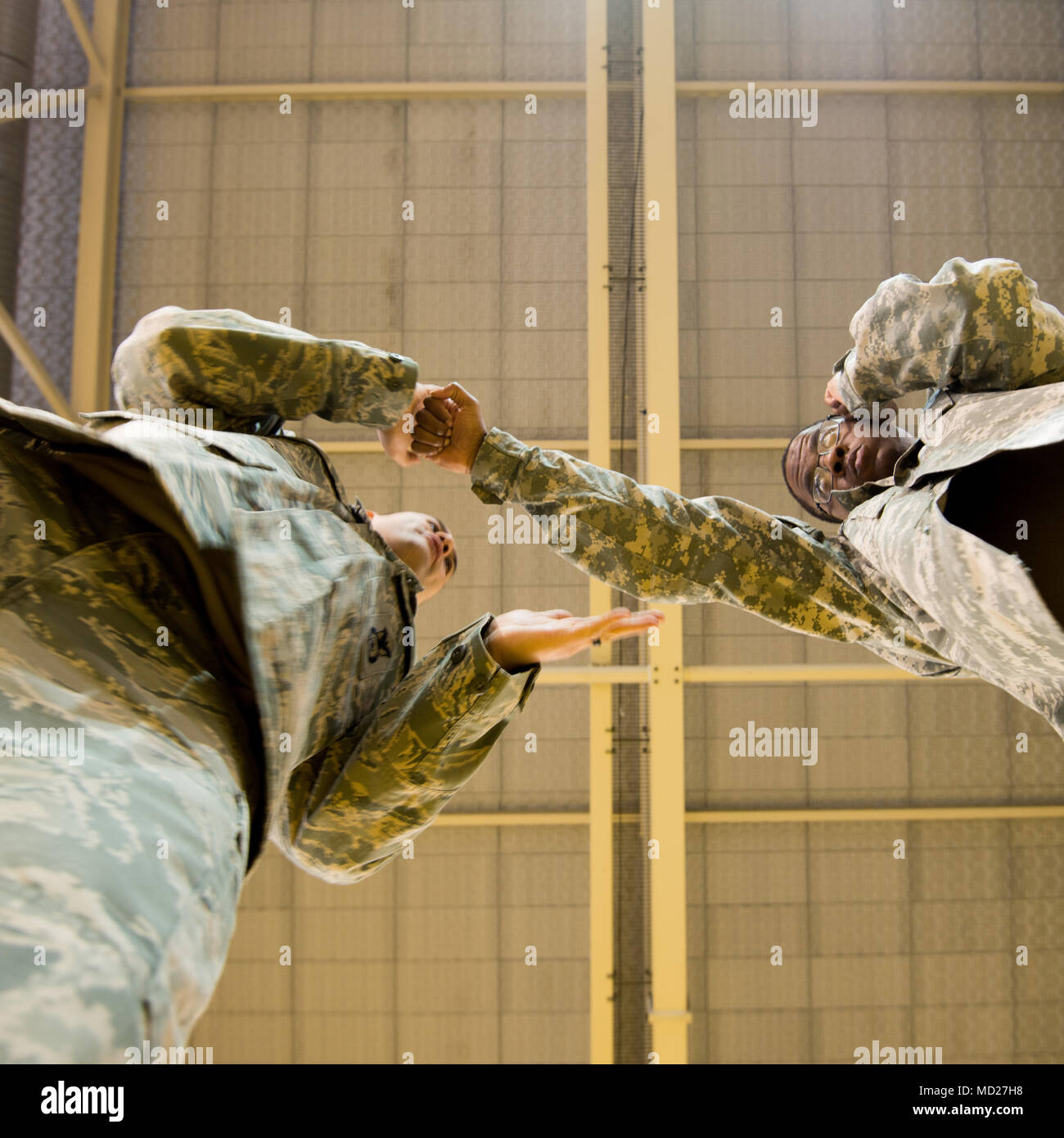 U.S. Air Force Staff Sgt. Mario Huerta, assigned to the SACEUR Security Detachment, describes the jab that U.S. Army Terrance Simmons, with the Northern Law Center, 21st Theater Sustainment Command throws, for a Joint Tactical Combatives Course, in Chièvres, Belgium, March 09, 2018. (U.S. Army photo by Visual Information Specialist Pierre-Etienne Courtejoie) - Stock Image