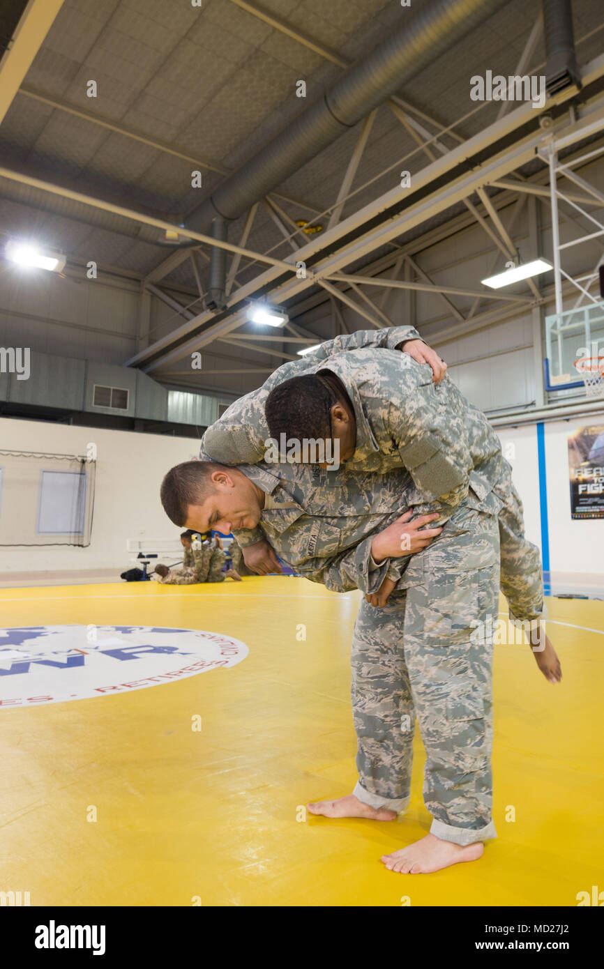 U.S. Air Force Staff Sgt. Mario Huerta , assigned to the SACEUR Security Detachment, performs a hip throw on U.S. Army   Sgt. Terrance Simmons, with the Northern Law Center, 21st Theater Sustainment Command, during the Joint Tactical Combatives Course, on Chièvres, Belgium, March 09, 2018. (U.S. Army photo by Visual Information Specialist Pierre-Etienne Courtejoie) - Stock Image