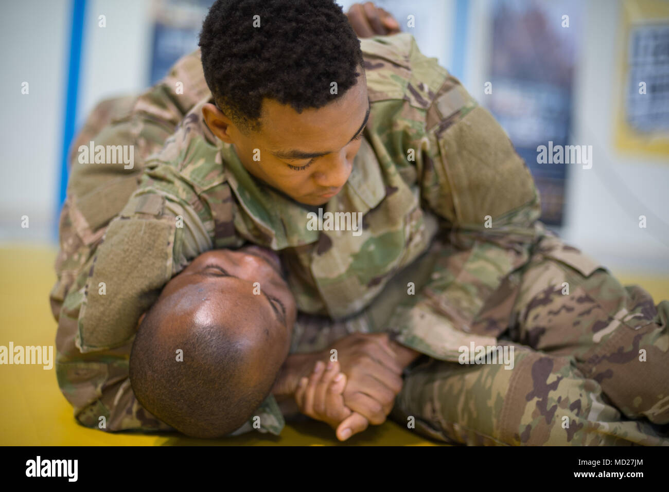 U.S. Army Pfc. Henry Tillman, with Headquarters and Headquarters Detachment, 39th Strategic Signal Battalion, headlocks Staff Sgt. Richard Amoah, assigned to Benelux Finance, 226th Financial Management Support Center, 21st Theater Sustainment Command, during the Joint Tactical Combatives Course, on Chièvres Air Base, Belgium, March 9, 2018. (U.S. Army photo by Visual Information Specialist Pierre-Etienne Courtejoie) - Stock Image