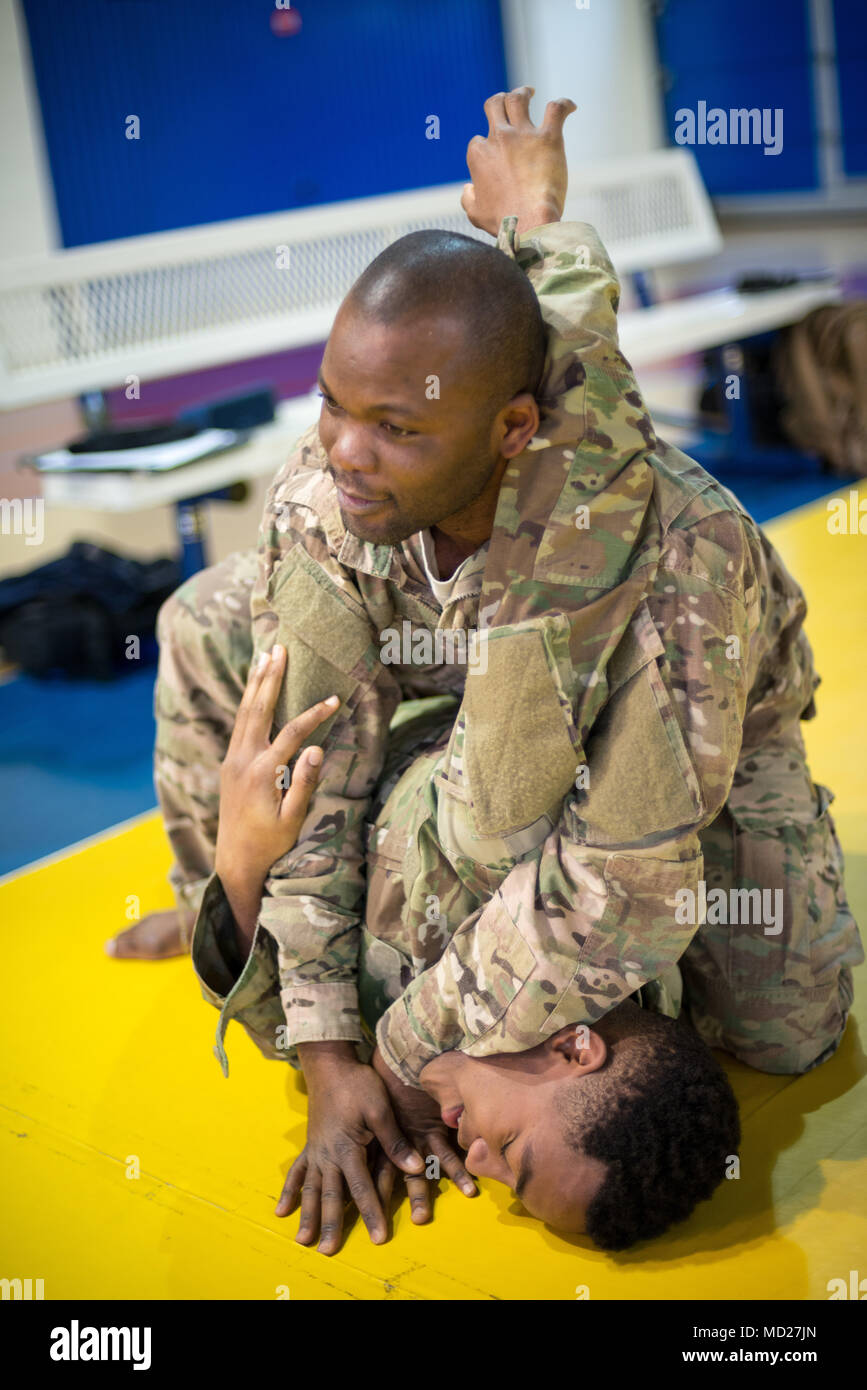 U.S. Army Staff Sgt. Richard Amoah, assigned to Benelux Finance, 226th Financial Management Support Center, 21st Theater Sustainment Command, escapes the headlock from Pfc. Henry Tillman, with Headquarters and Headquarters Detachment, 39th Strategic Signal Battalion, during the Joint Tactical Combatives Course, on Chièvres Air Base, Belgium, March 9, 2018. (U.S. Army photo by Visual Information Specialist Pierre-Etienne Courtejoie) - Stock Image