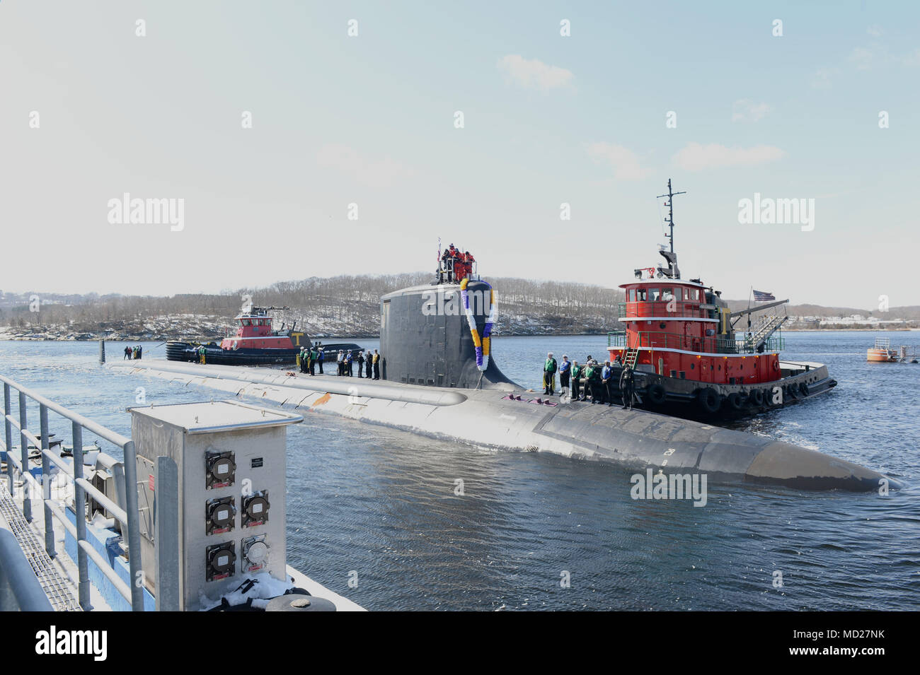 180314-N-LW591-010 GROTON, Conn. (Mar. 14, 2018) Sailors assigned to the Virginia-class, nuclear-powered, fast-attack submarine, USS Minnesota (SSN-783),  stand topside as their friends and families cheer their arrival as Minnesota pulls into its homeport on Naval Submarine Base New London in Groton, Conn., on Wednesday 14, Mar. Minnesota is returning from the European Command Area of Responsibility where they executed the Chief of Naval Operation's Maritime Strategy in supporting national security interests and Maritime Security Operations. (U.S. Navy photo by Mass Communication Specialist 1s - Stock Image