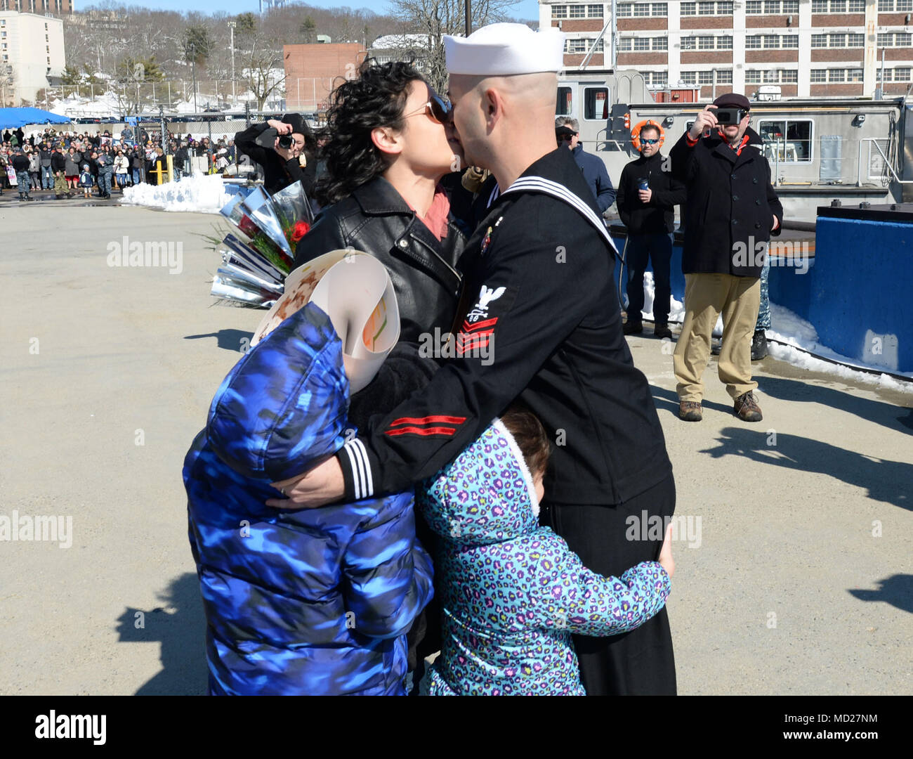 180314-N-LW591-013 GROTON, Conn. (Mar. 14, 2018) Sonar Technician Submarine 1st Class Michael Acosta is greeted by his wife, Ilvia Acosta with the traditional first kiss as his kids embrace him with hugs during a homecoming celebration for the Virginia-class, nuclear-powered, fast-attack submarine, USS Minnesota (SSN-783), on Naval Submarine Base, New London in Groton, Conn., on Wednesday 14, Mar. Minnesota is returning from the European Command Area of Responsibility where they executed the Chief of Naval Operation's Maritime Strategy in supporting national security interests and Maritime Sec - Stock Image