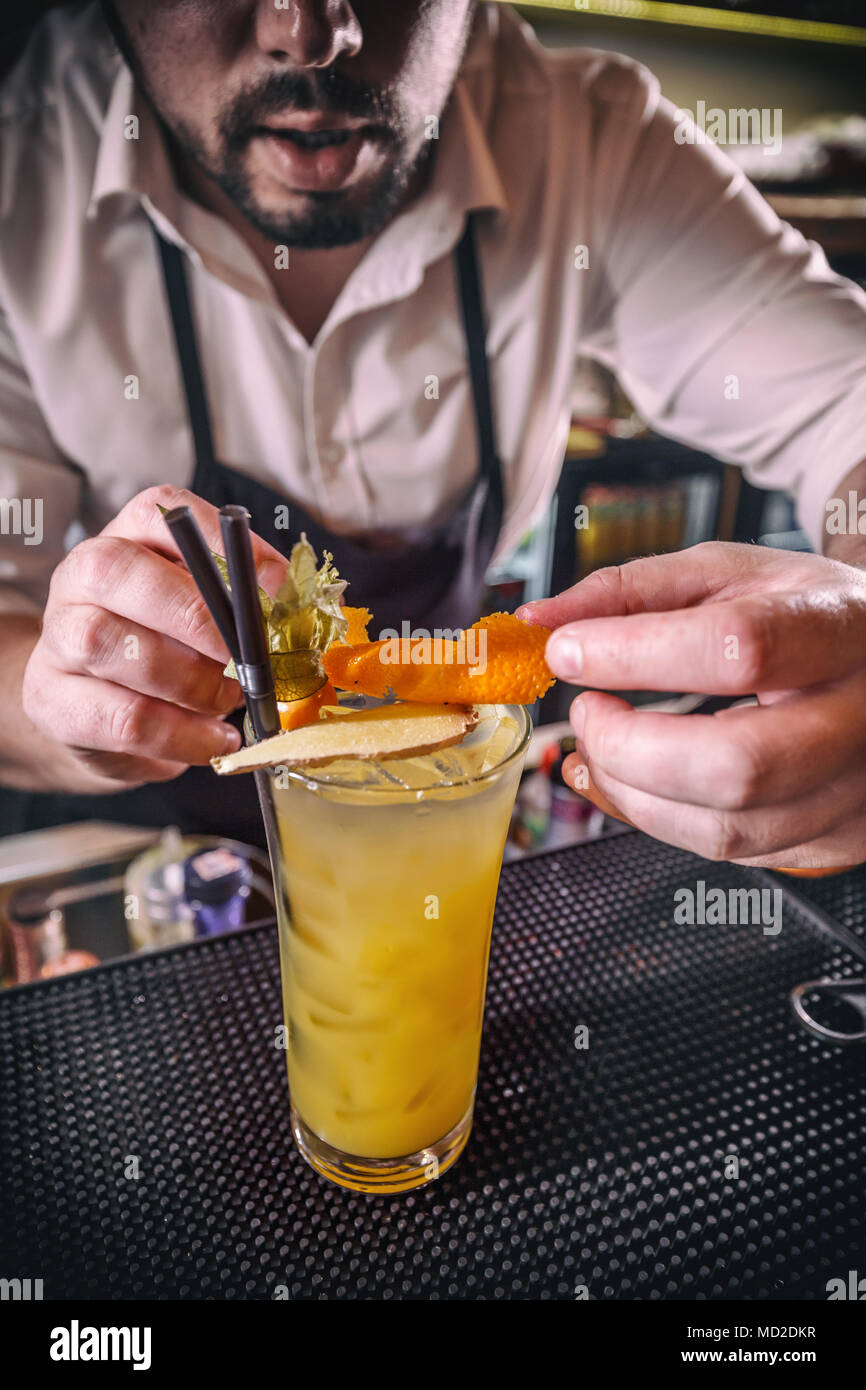 Barman is decorating non-alcoholic cocktail with orange zest - Stock Image