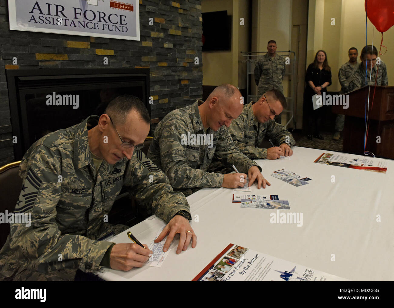 (from left) Chief Master Sgt. Lee Mills, 92nd Air Refueling Wing command chief, Col. Ryan Samuelson, 92nd ARW commander, and Col. J. Scot Heathman, 92nd ARW vice commander, make the first donations during the Air Force Assistance Fund kick-off breakfast at Fairchild Air Force Base, Washington, March 26, 2018. The Air Force Aid Society directs the AFAF and works to support and enhance the U.S. Air Force mission by providing emergency financial assistance, education support and community programs to Airmen. - Stock Image