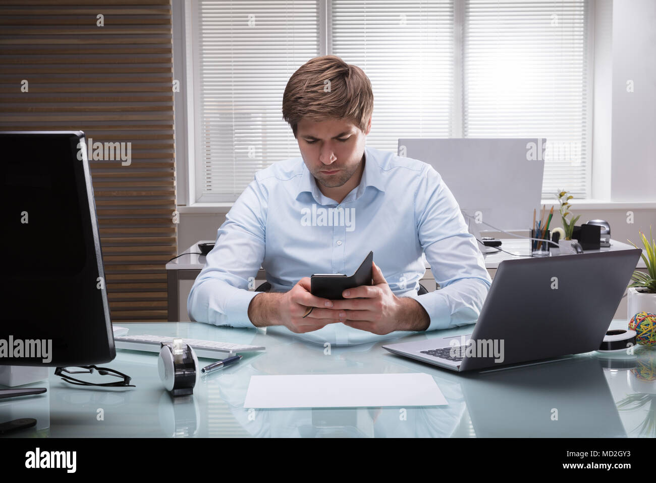 Young Businessman Sitting In Office Using Mobile Phone Stock Photo