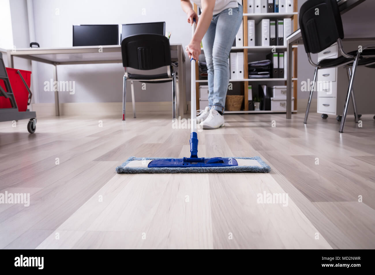 Janitor's Hand Cleaning Floor With Mop At Workplace - Stock Image