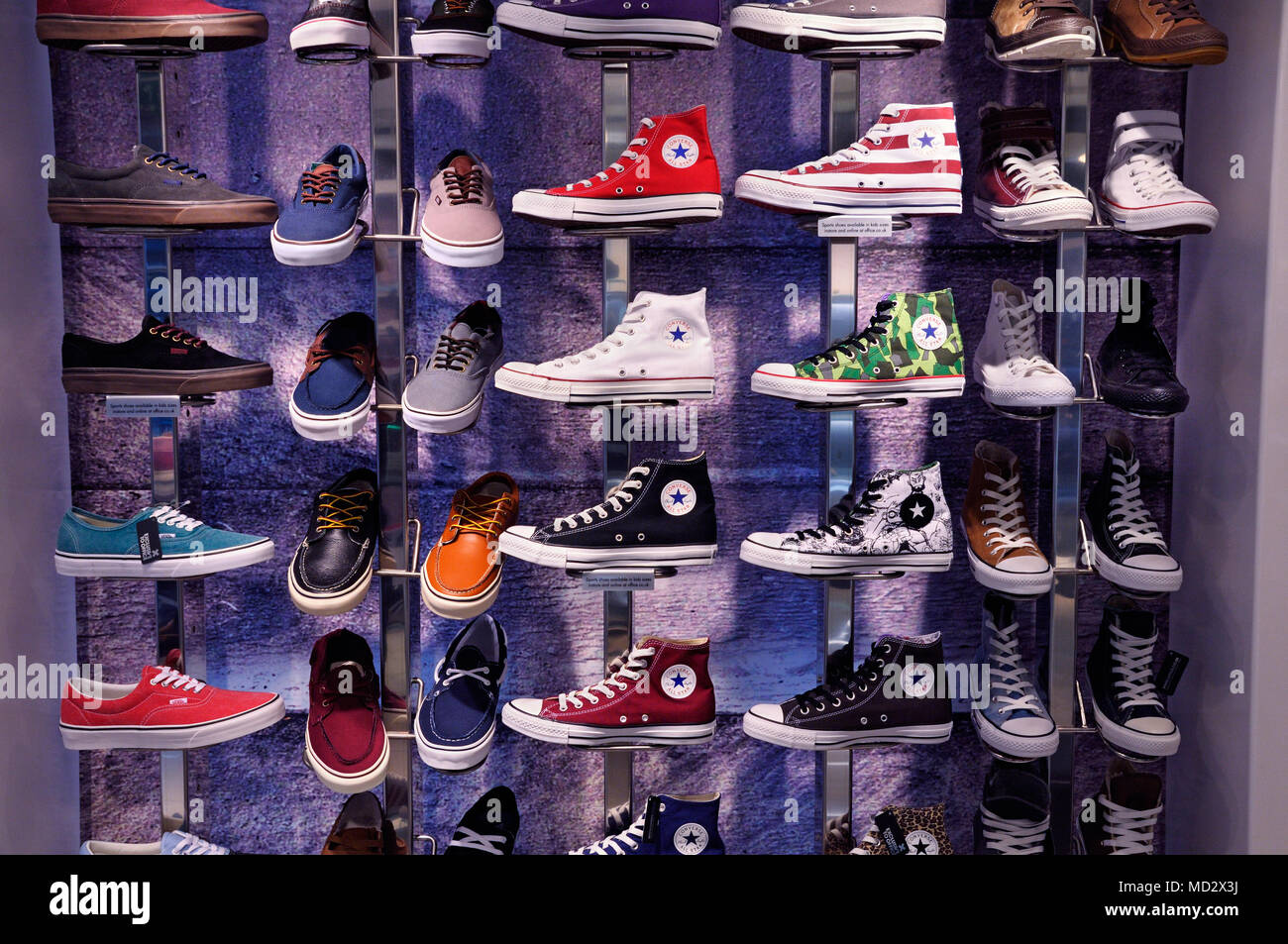 Converse trainers and Vans shoes in shop display - Stock Image