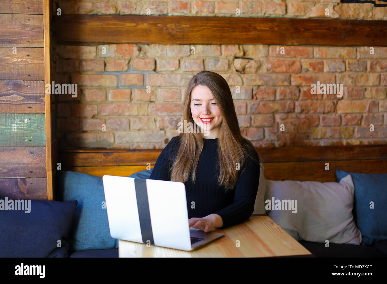 Woman with red lips using laptop at cafe. - Stock Image