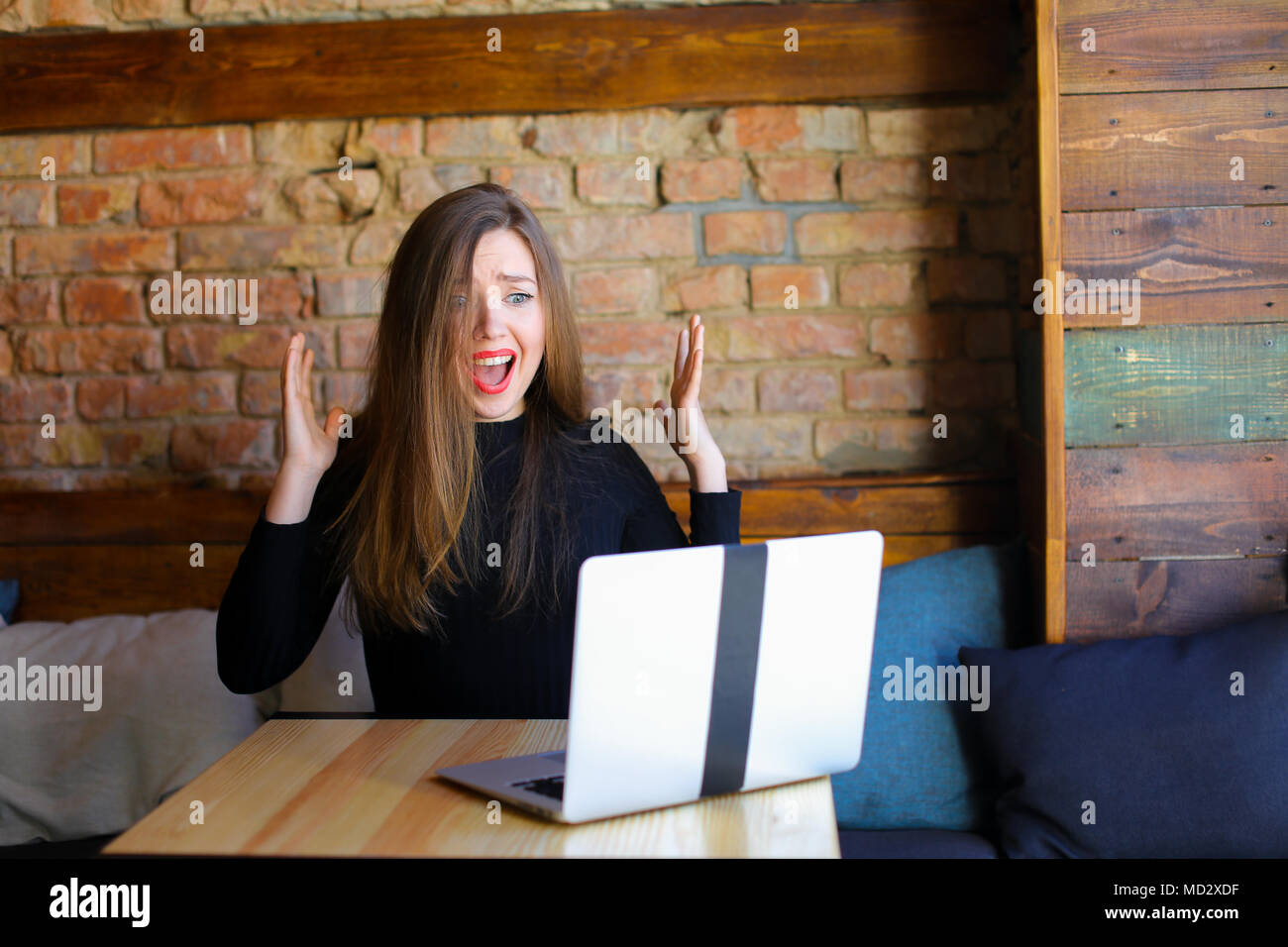 Shocked female person using laptop and sitting at cafe. - Stock Image