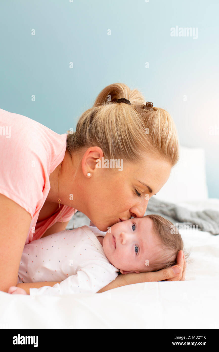 young, beautiful and blond mother with pink shirt is cuddling with her baby in bed - Stock Image