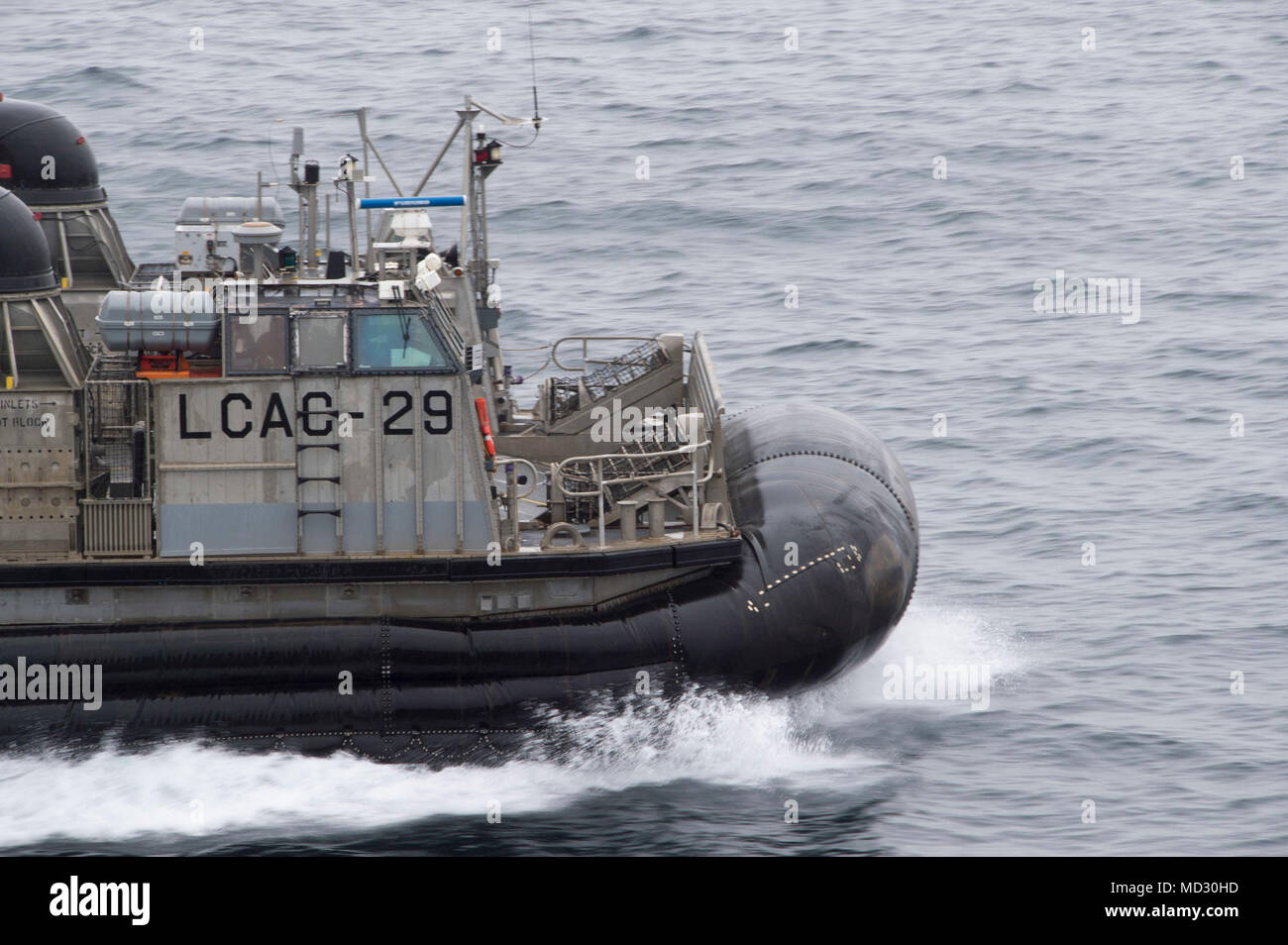 180417-N-FF029-032 SASEBO, Japan (April 17, 2018) Landing craft air cushion (LCAC) 29, assigned to Naval Beach Unit (NBU) 7, disembarks the amphibious assault ship USS Bonhomme Richard (LHD 6). The debarkation marks NBU 7's final deployment with Bonhomme Richard as the ship prepares for a homeport shift to San Diego after six years of being forward-deployed to Sasebo, Japan. (U.S. Navy photo by Mass Communication Specialist 3rd Class Daniel Charest/Released) - Stock Image