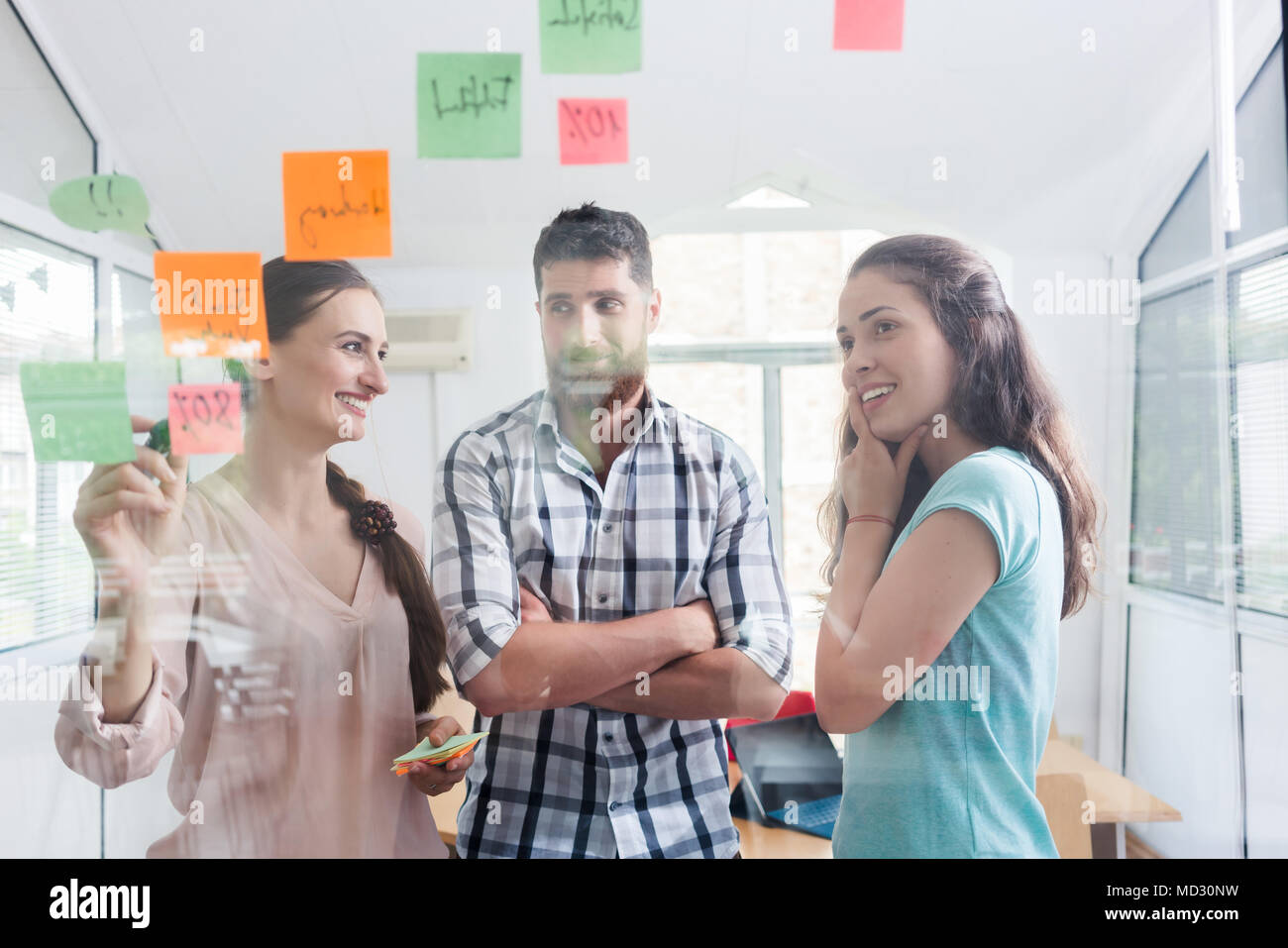 Reliable young workers posting reminders in a modern co-working space - Stock Image